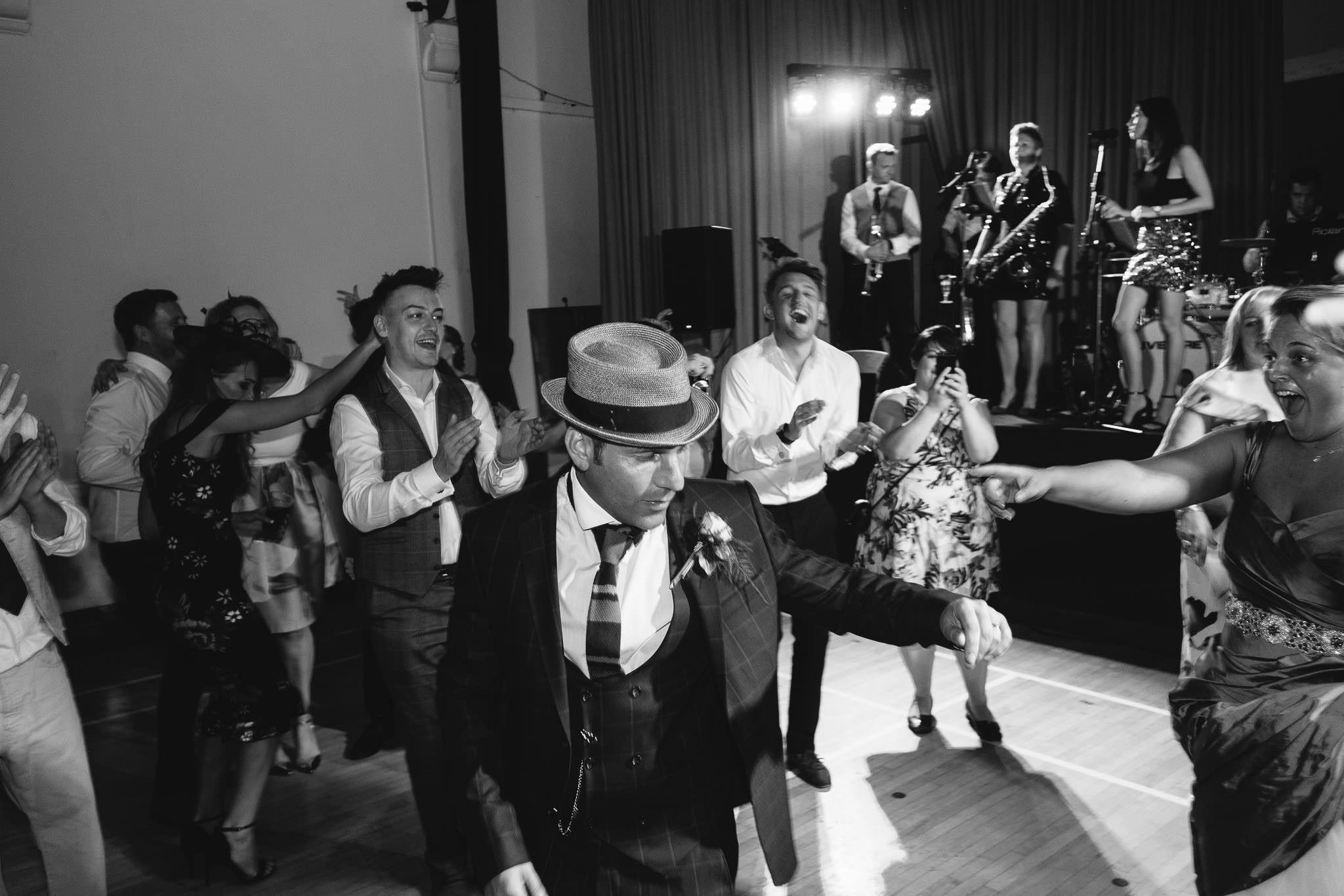 A black and white photo of the groom dancing while wearing a hat