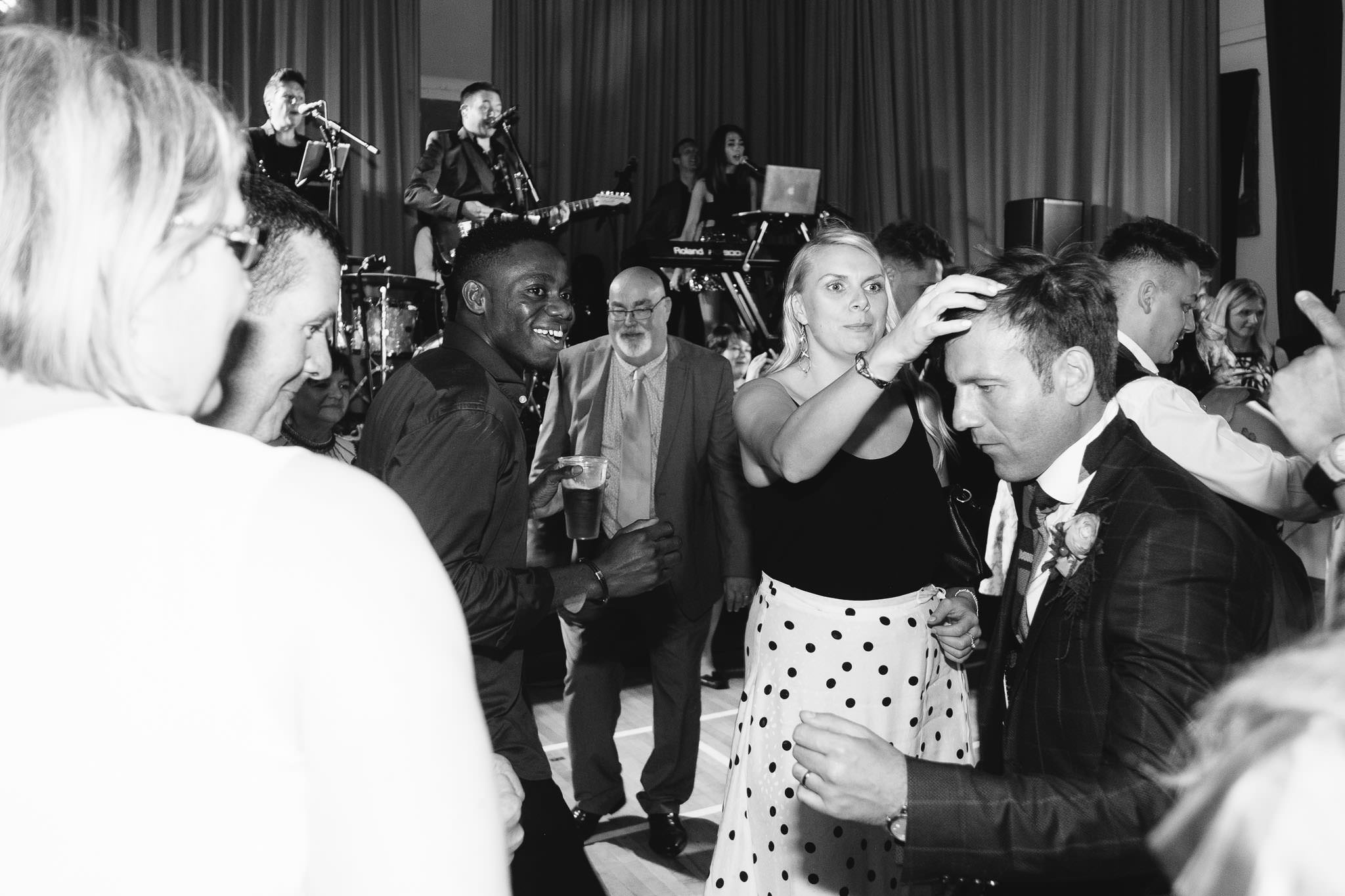 A black and white photo of a guest ruffling the groom's hair on the dance floor