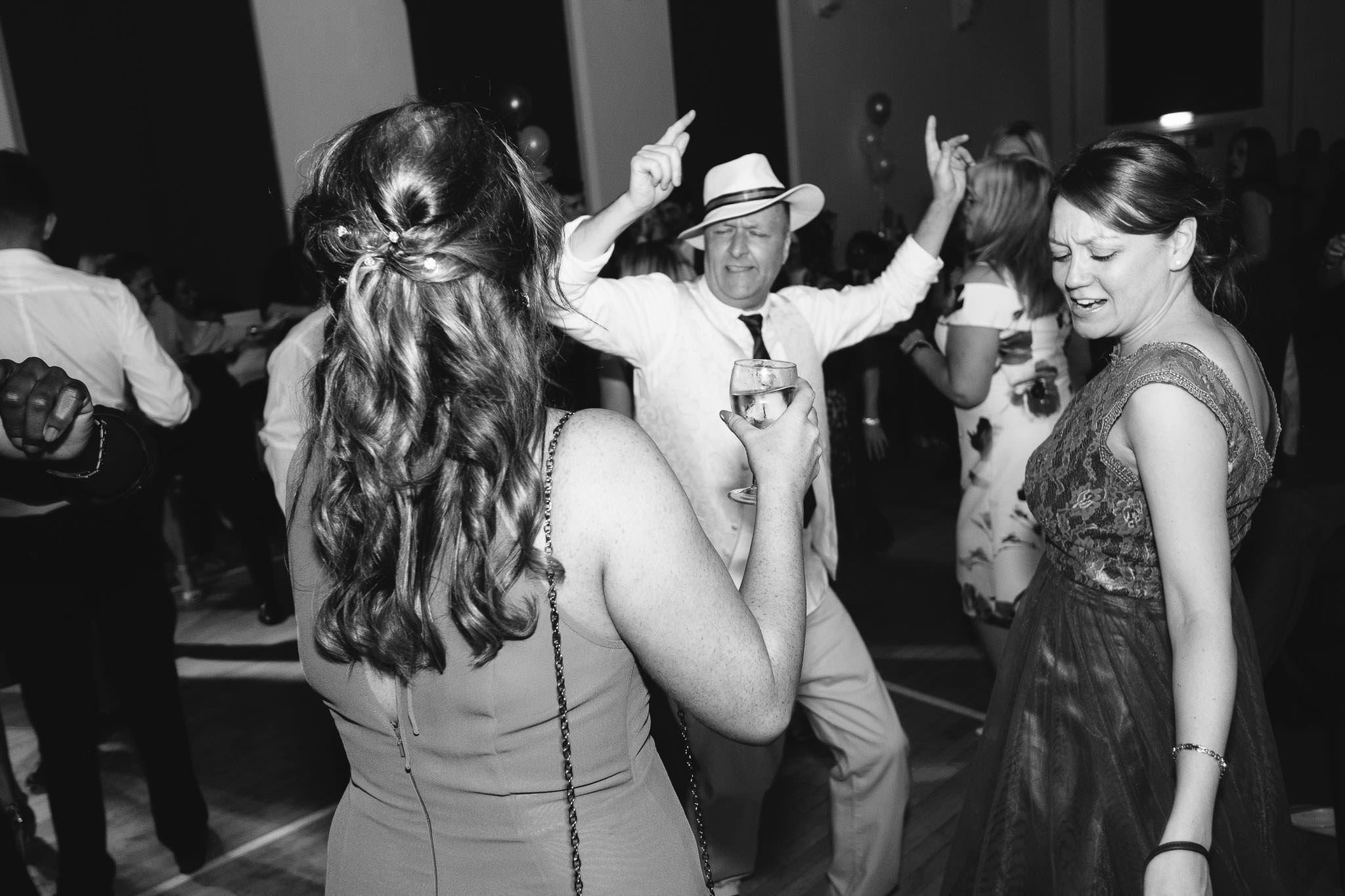 A black and white photo of a wedding guest and the bridesmaids dancing