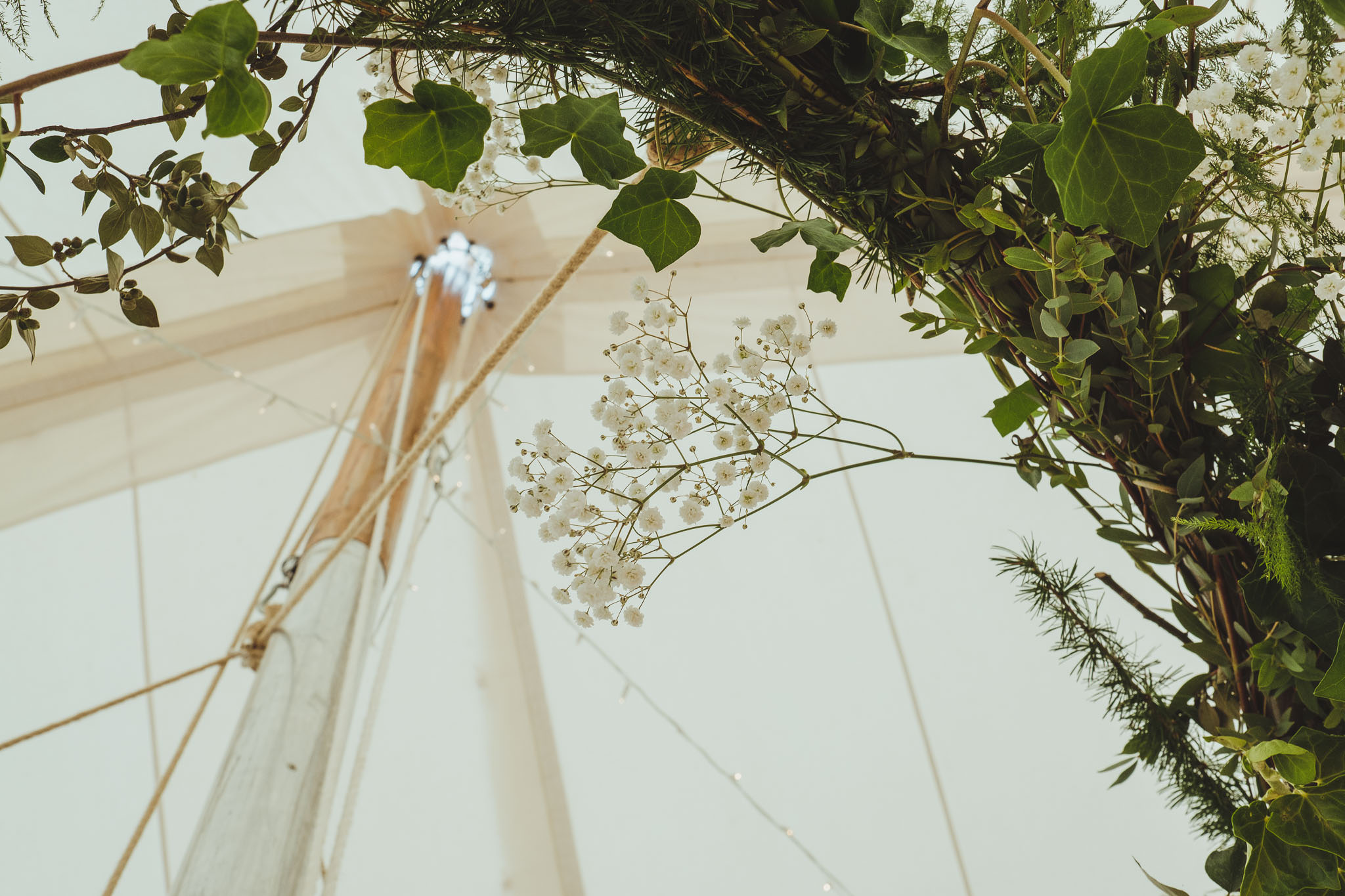Close up of decorative foliage inside the wedding marquee