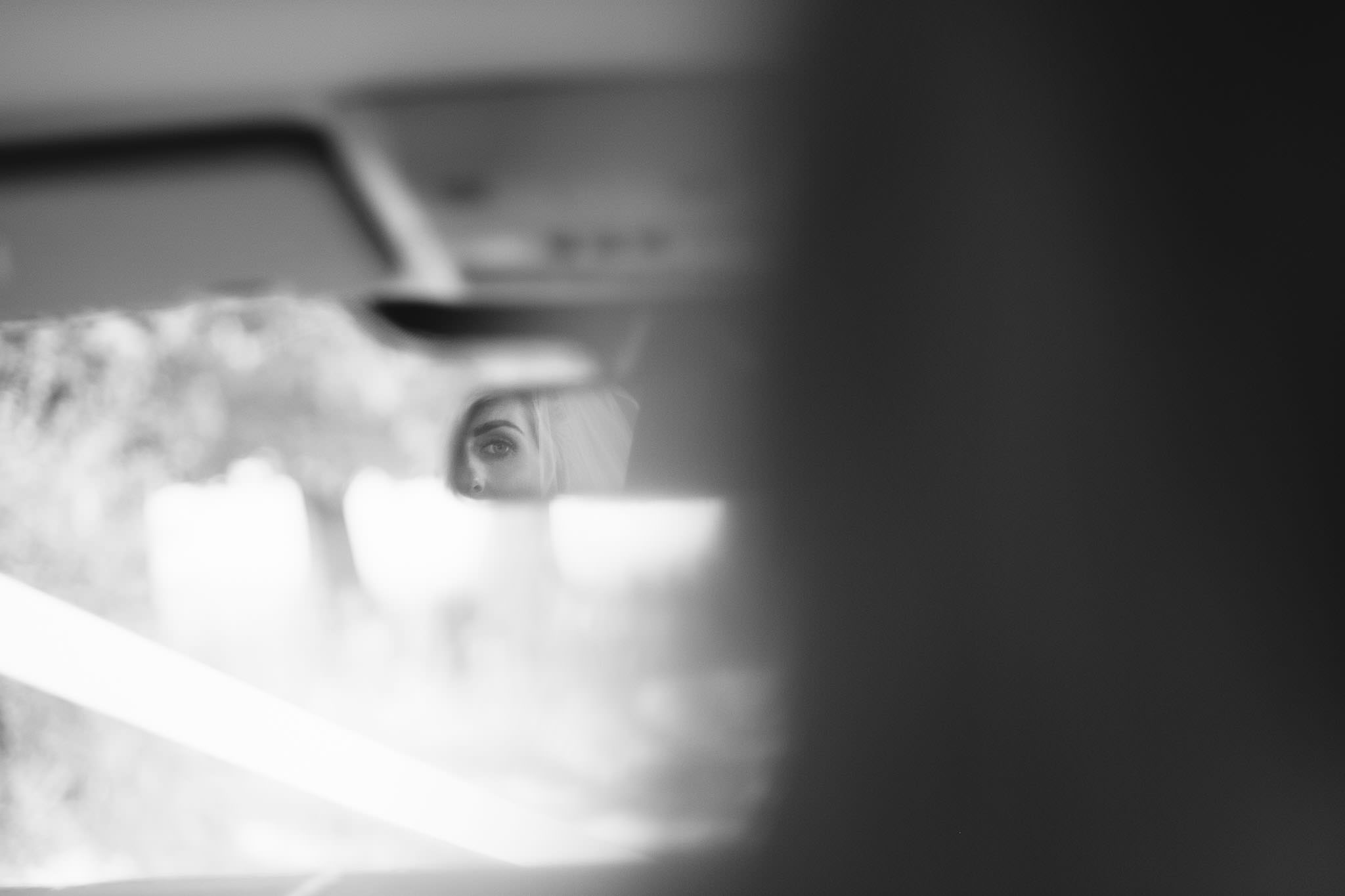 A black and white photo of the bride's eye reflected in the car mirror