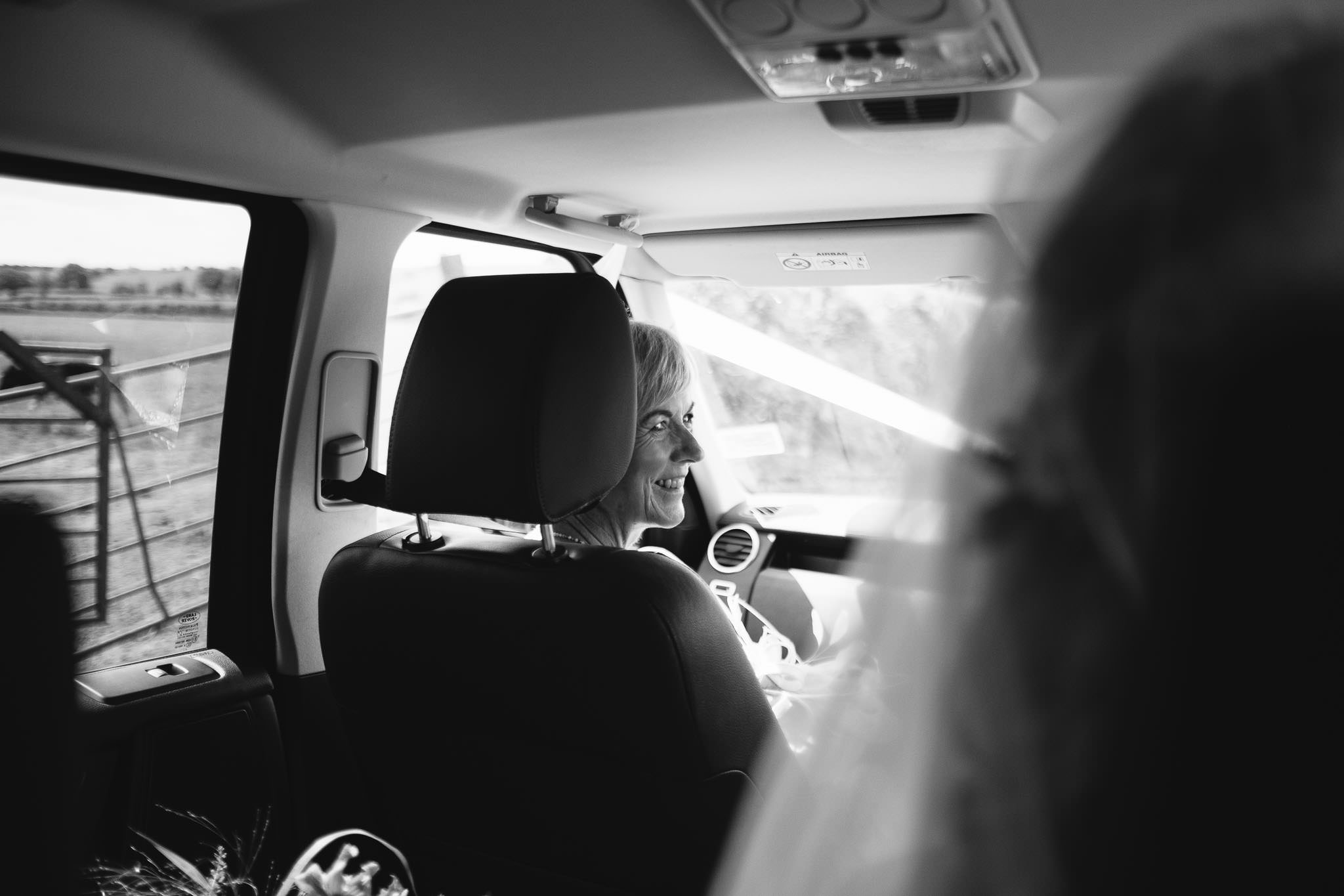 A black and white photo of the bride's mother looking at her daughter in the wedding car