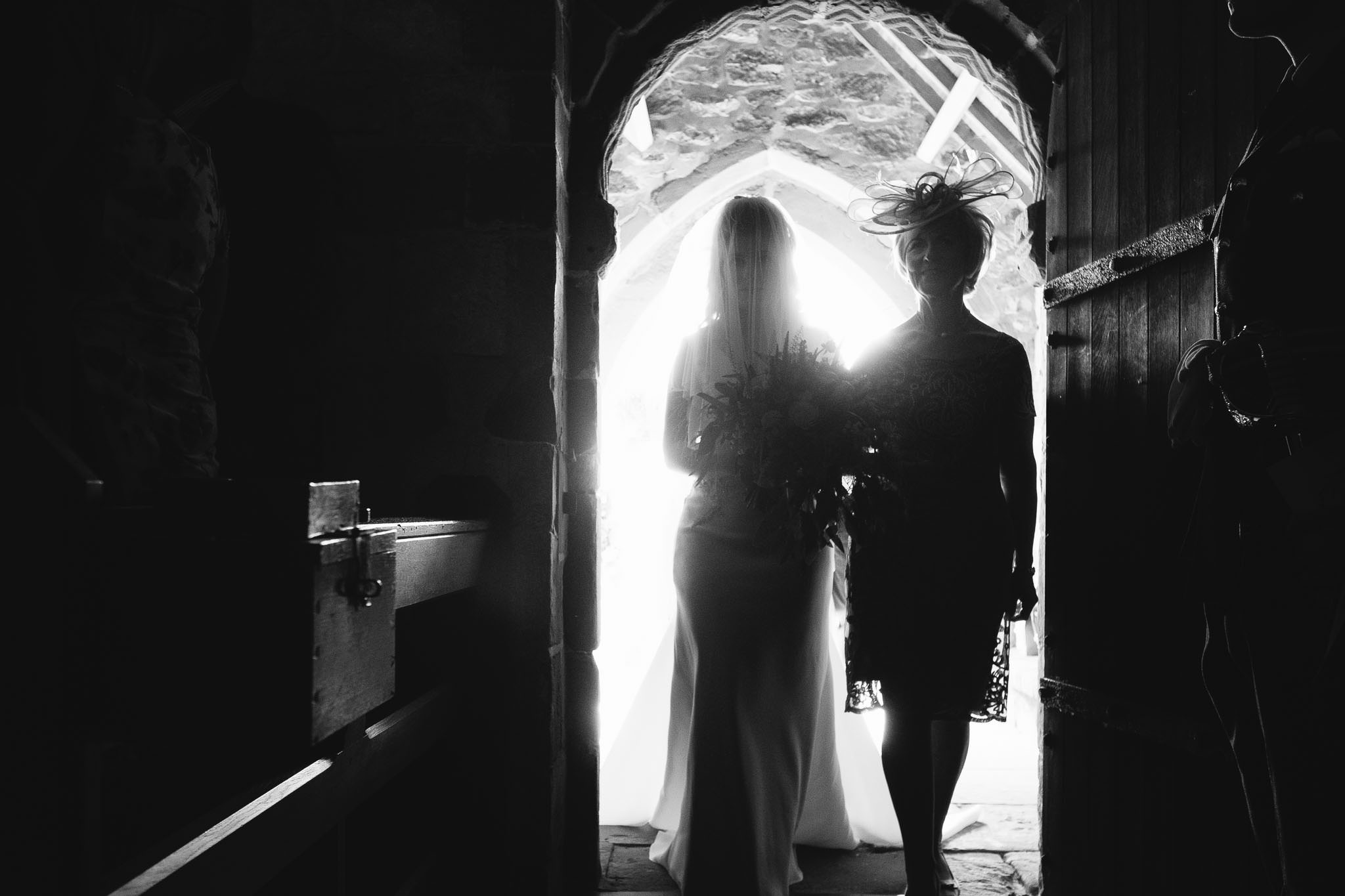 A black and white photo of the bride entering the church with her mother