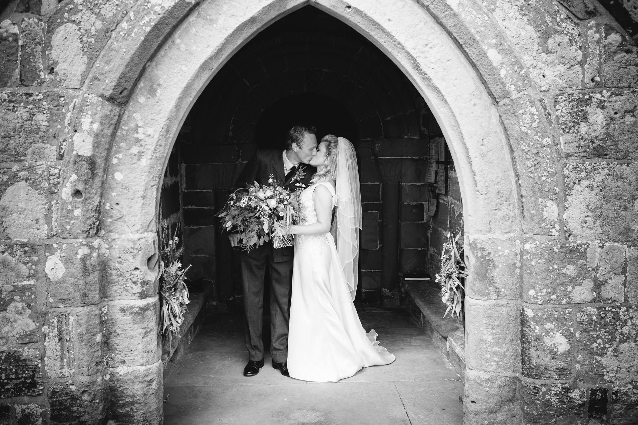 A black and white photo of the bride and groom kissing in the archway of the church