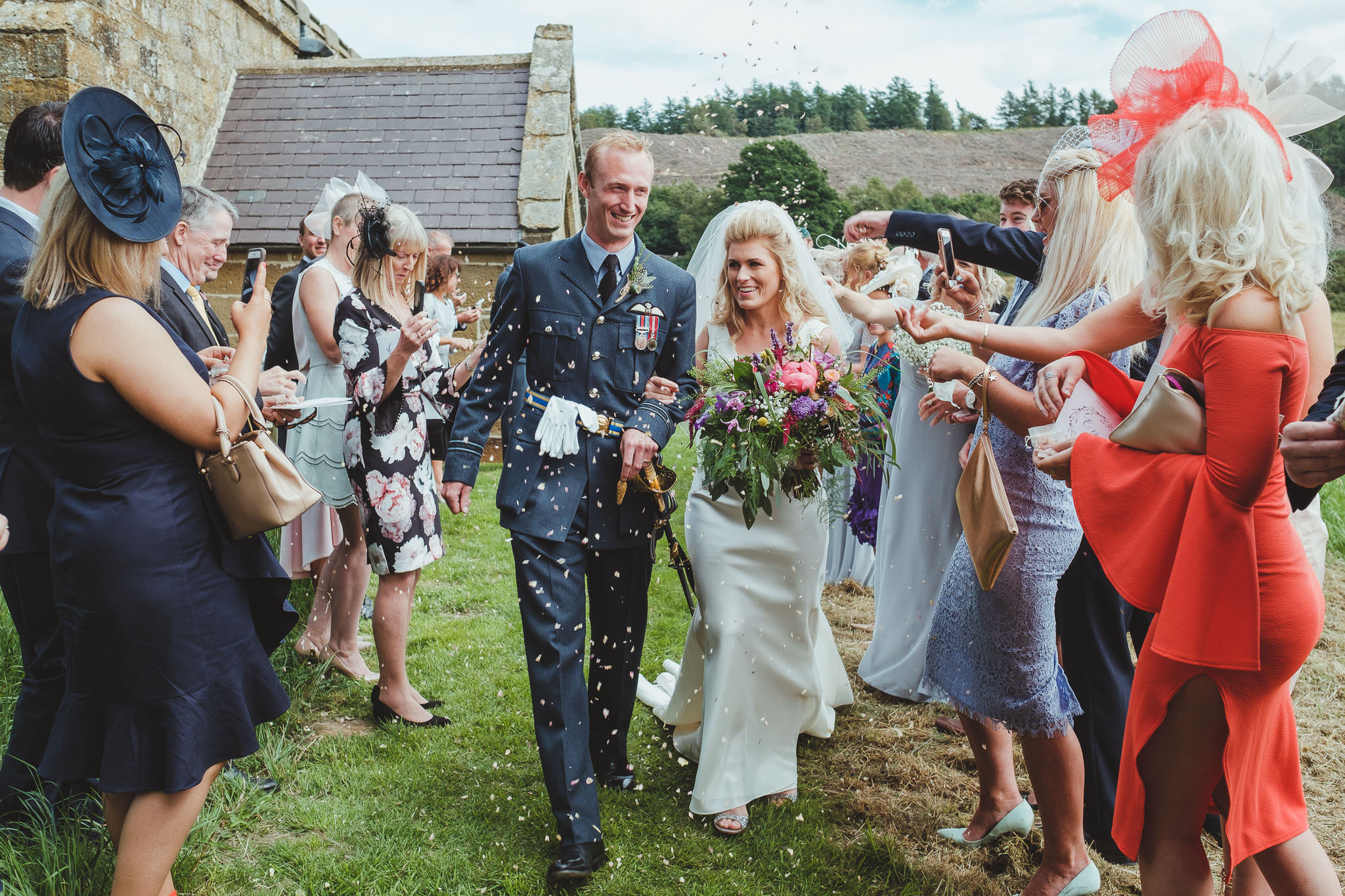 The bride and groom are showered with confetti by their guests