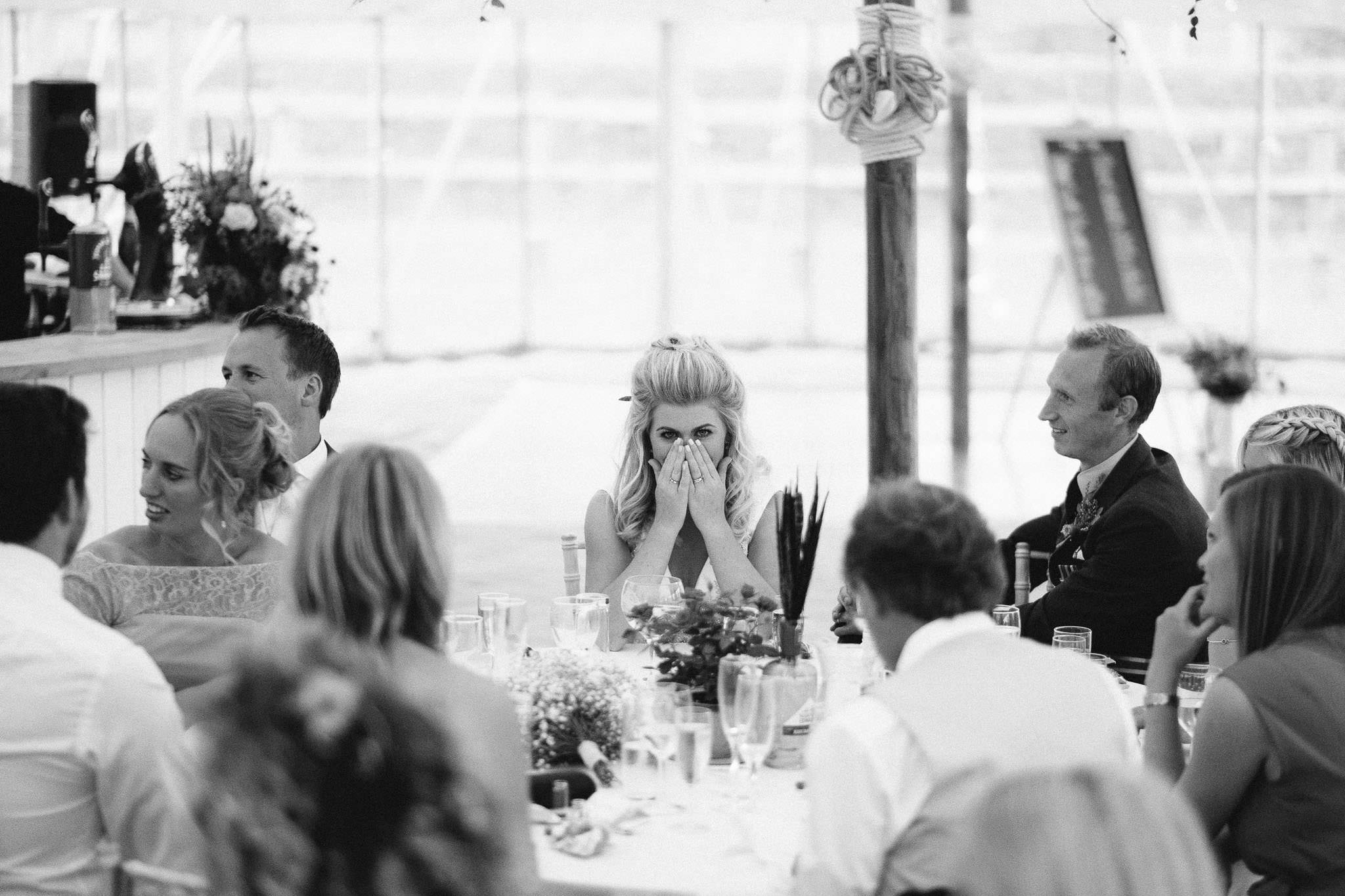 A black and white photo of the bride with her head in her hands during the wedding speeches