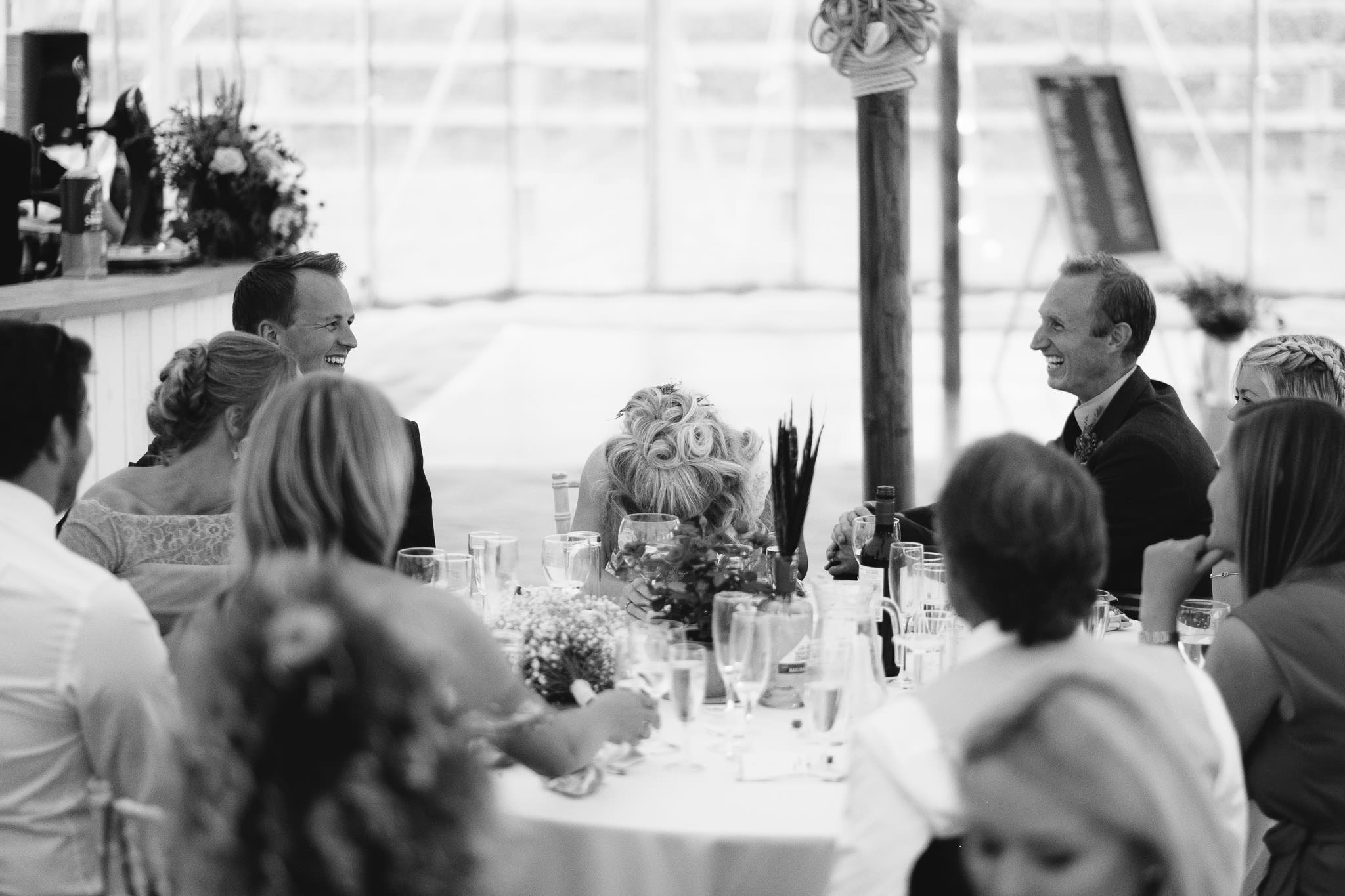 A black and white photo of the bride hiding her face during the wedding speeches