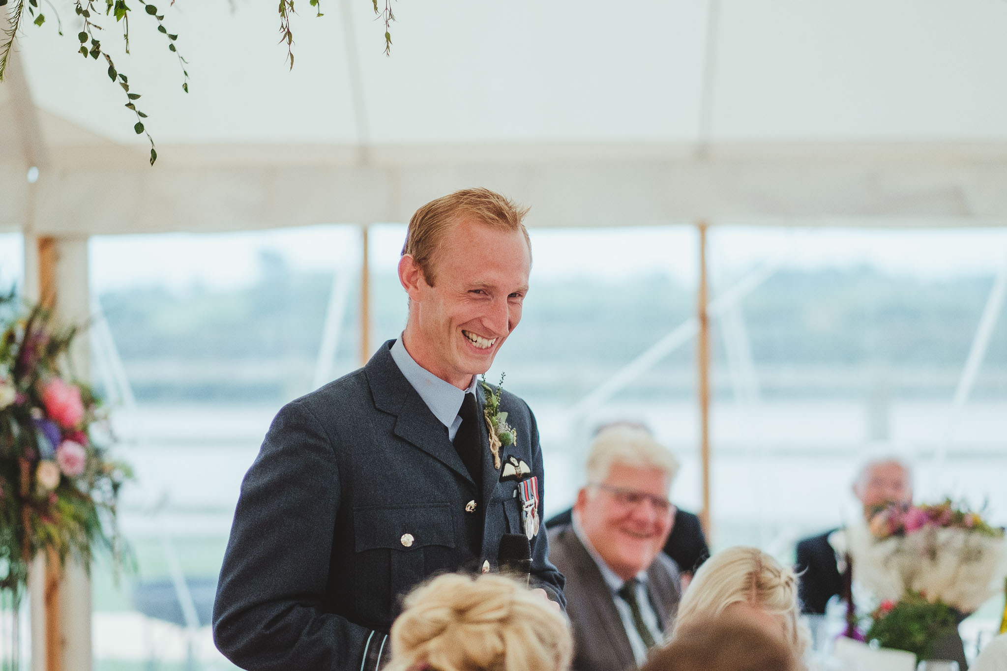 The groom laughing during his wedding speech