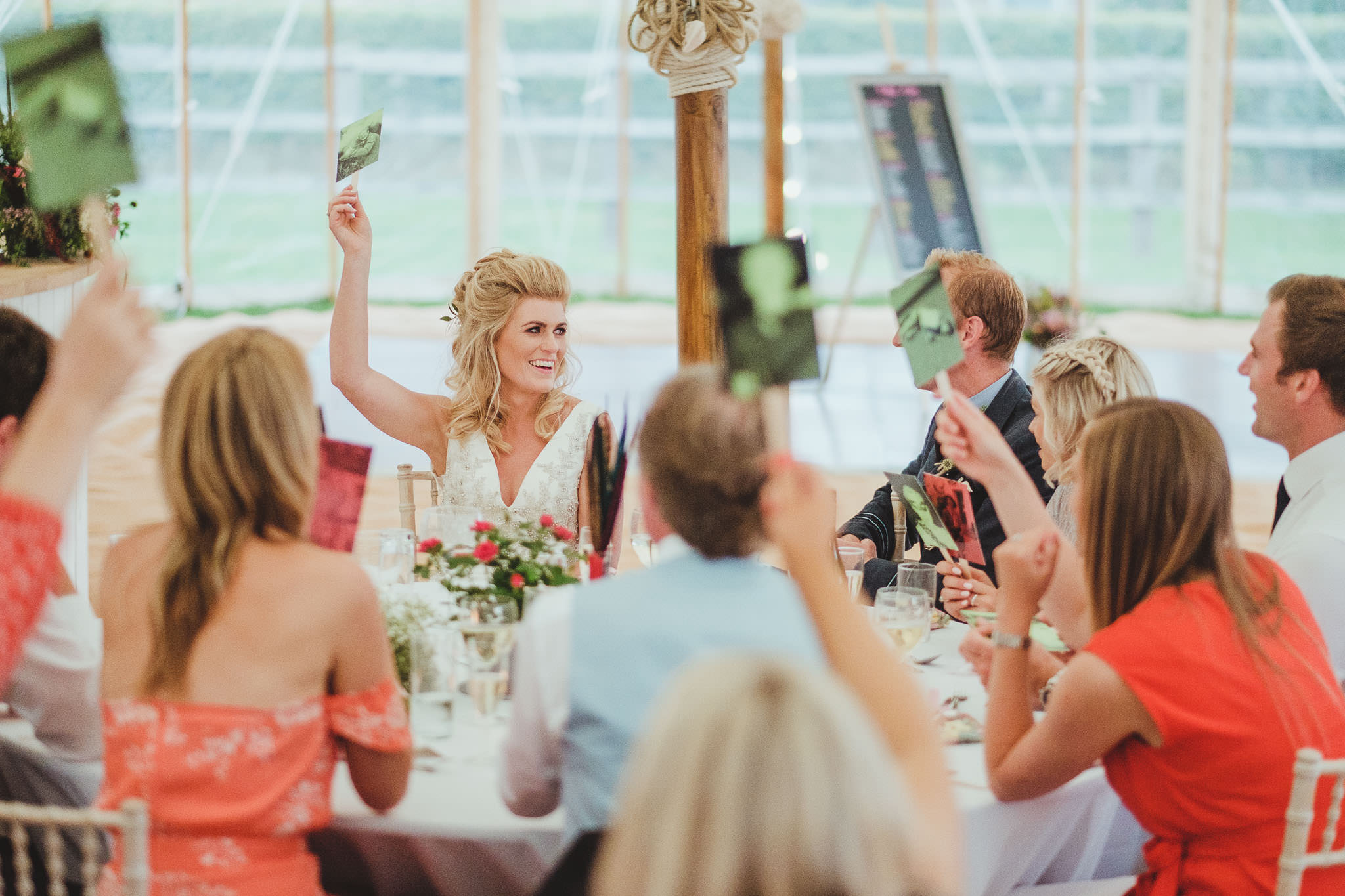 The bride laughs while playing a game during the wedding speeches