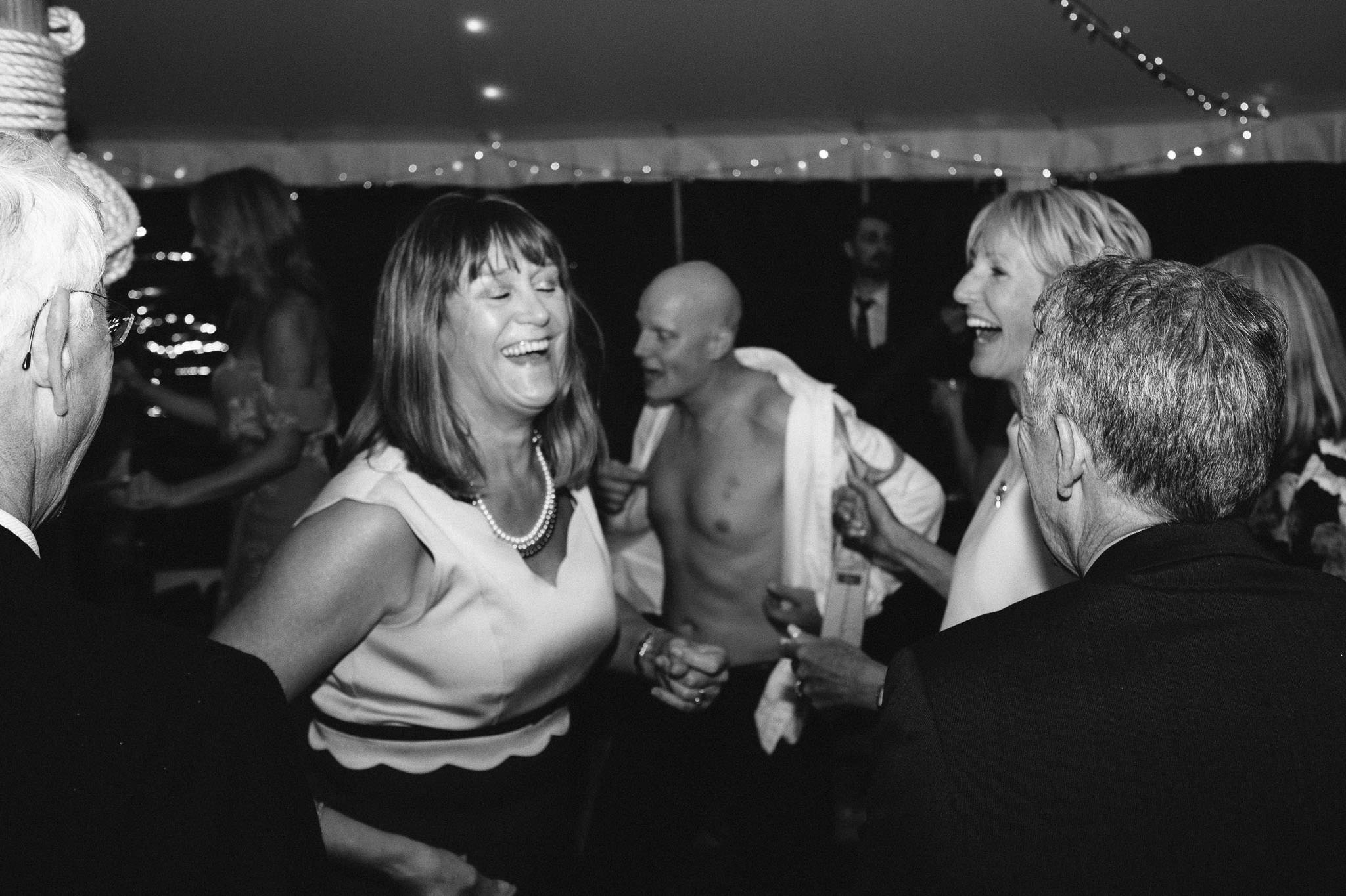 A black and white photo of wedding guests laughing at someone taking off his shirt on the dance floor