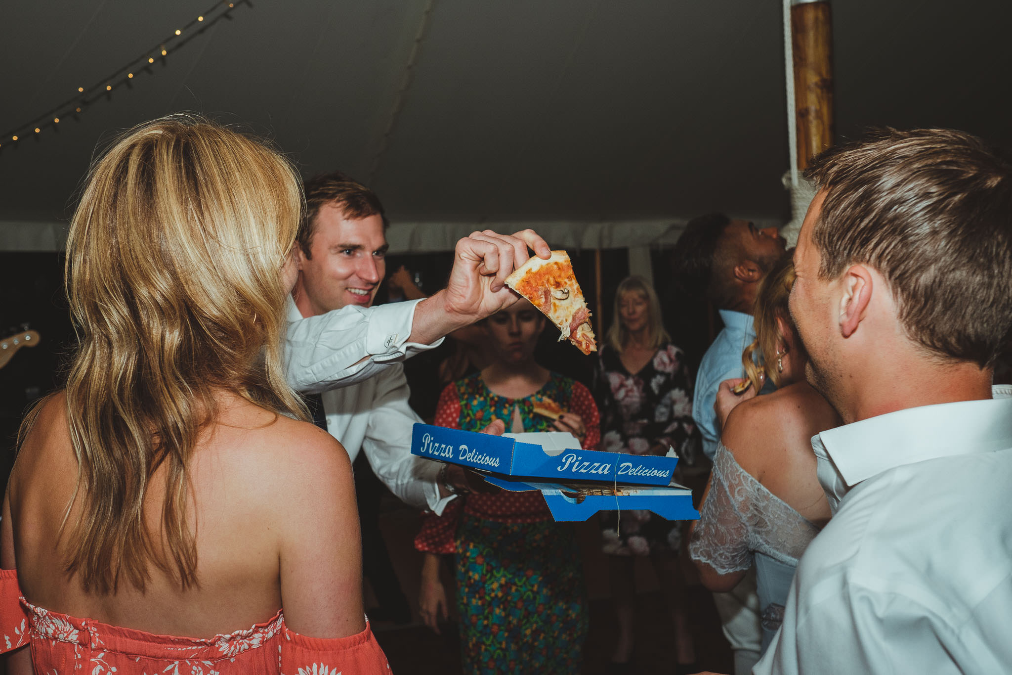 A wedding guest waves a slice of pizza on the dance floor