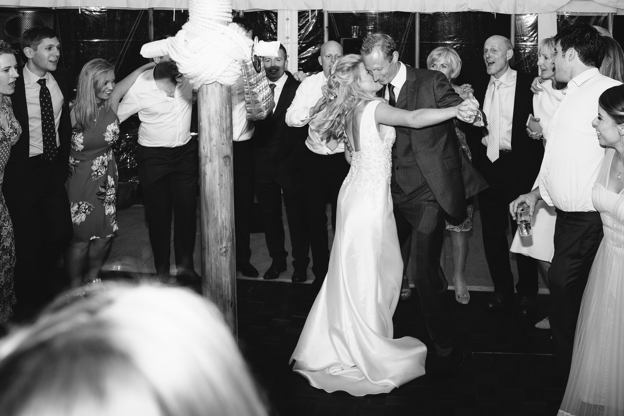 A black and white photo of the bride and groom dancing in front of their friends