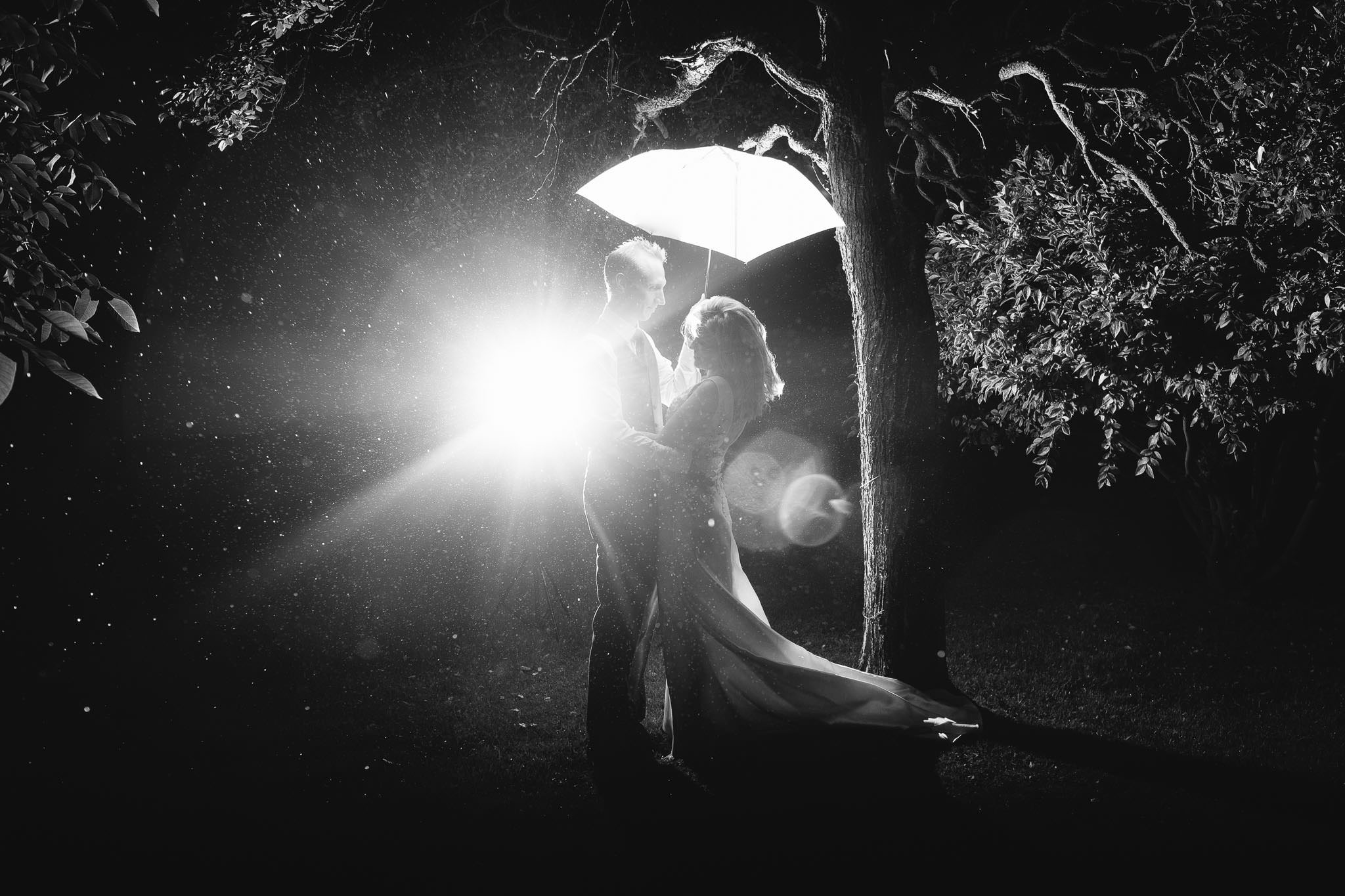 A black and white photo of the bride and groom under an umbrella in the rain with the flash bathing them in light