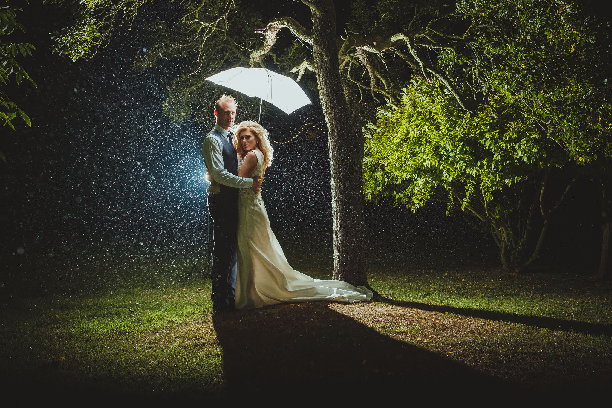 The bride and groom hug under an umbrella in the rain