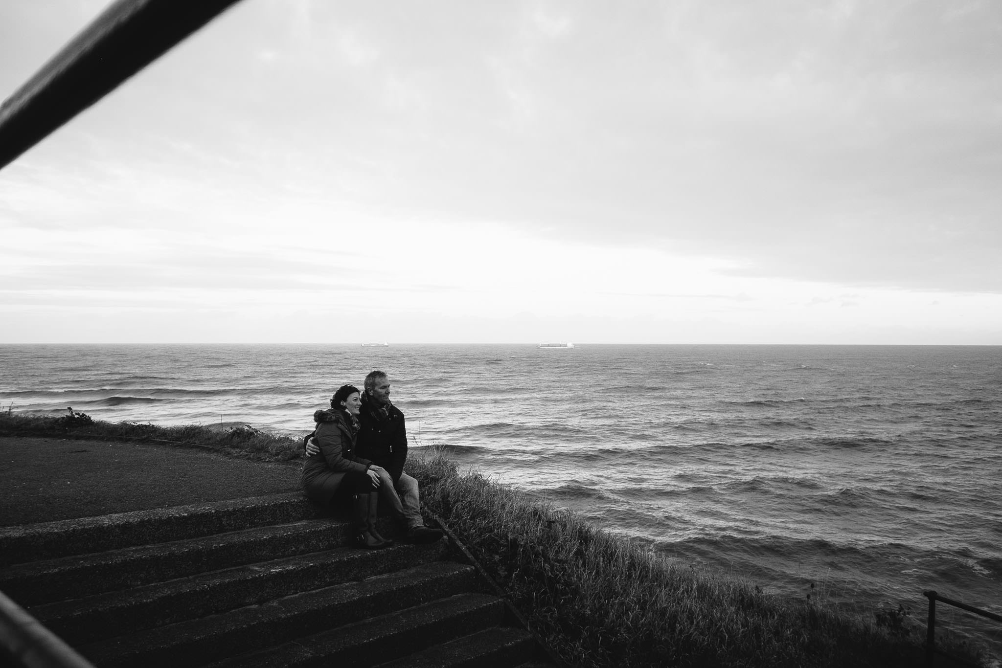 Black and white photo of couple sitting on steps looking out over the North Sea