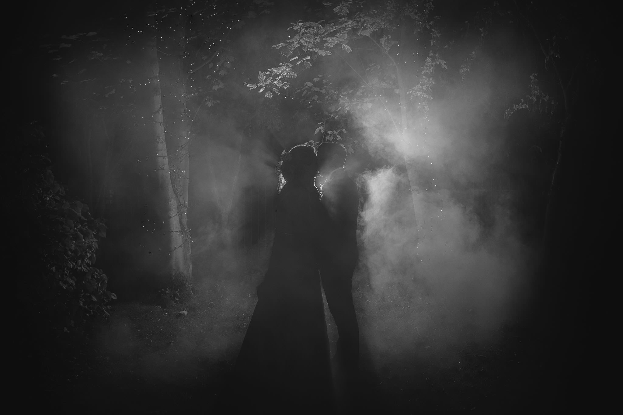 This was my favourite photo of all the ones I took. The flash made the couple into silhouettes, with a strongly defined rim light. The flash is punching through the smoke and giving a very romantic and dreamy mood. Combined with the twinkling strings of fairy lights and the trees it works very well to transform a tiny corner of a Mining Institute garden into something magical.
