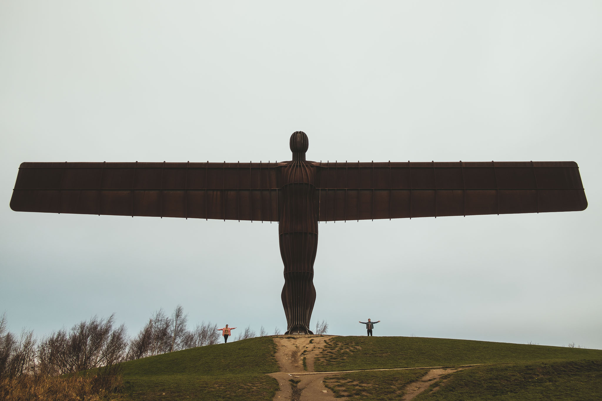 An engaged couple stand under the Angel of the North with their arms spread out wide