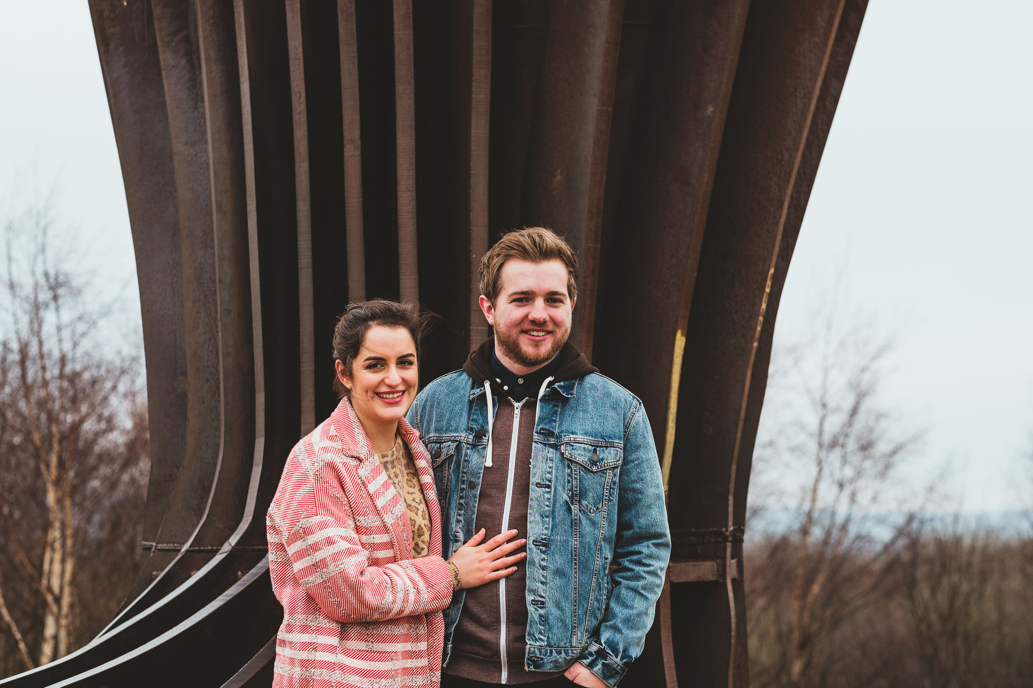 An engagement photo of a couple standing in front of the Angel of the North Gateshead
