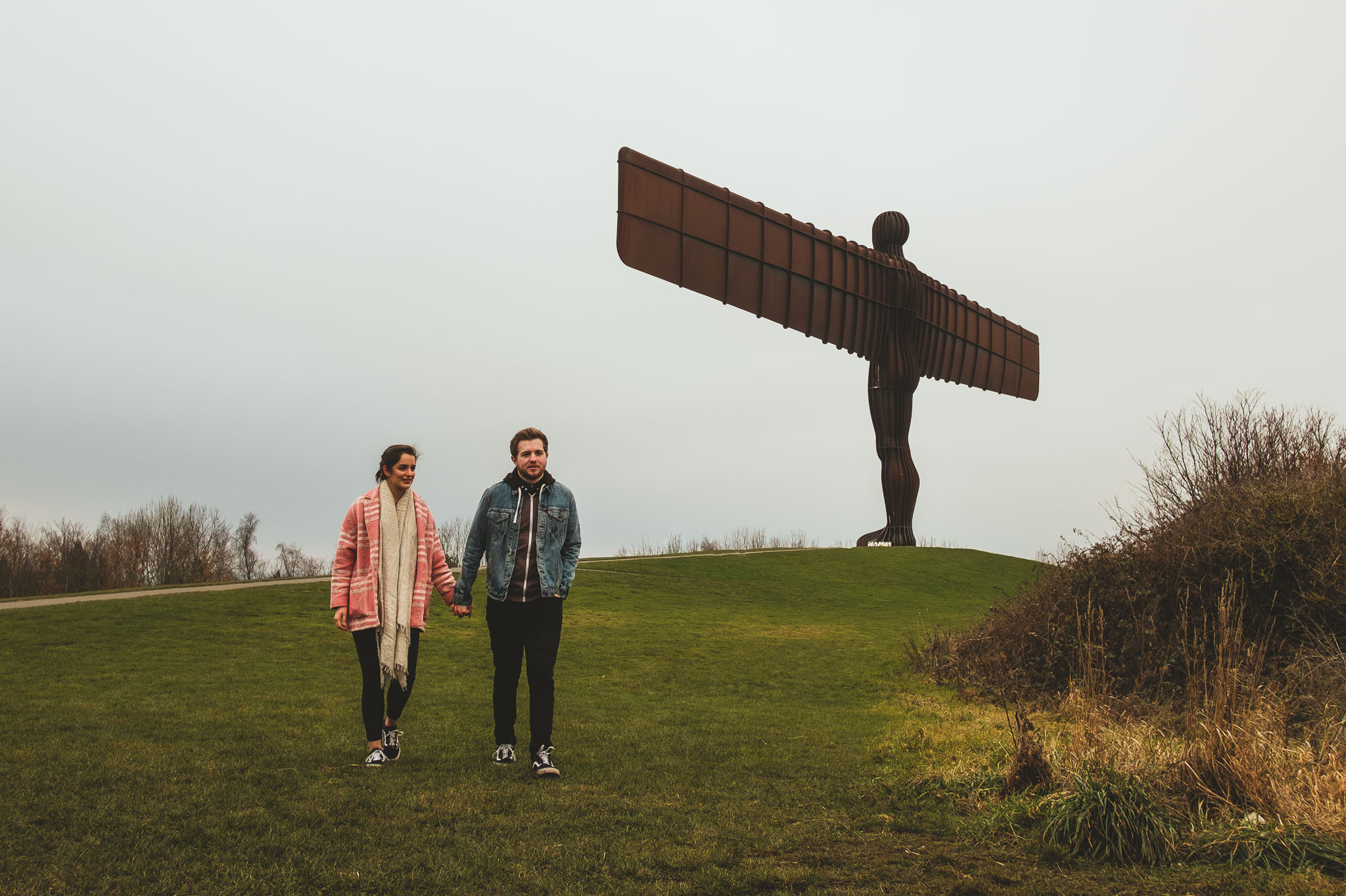 post wedding photo of a couple walking away from the Angel of the North while holding hands