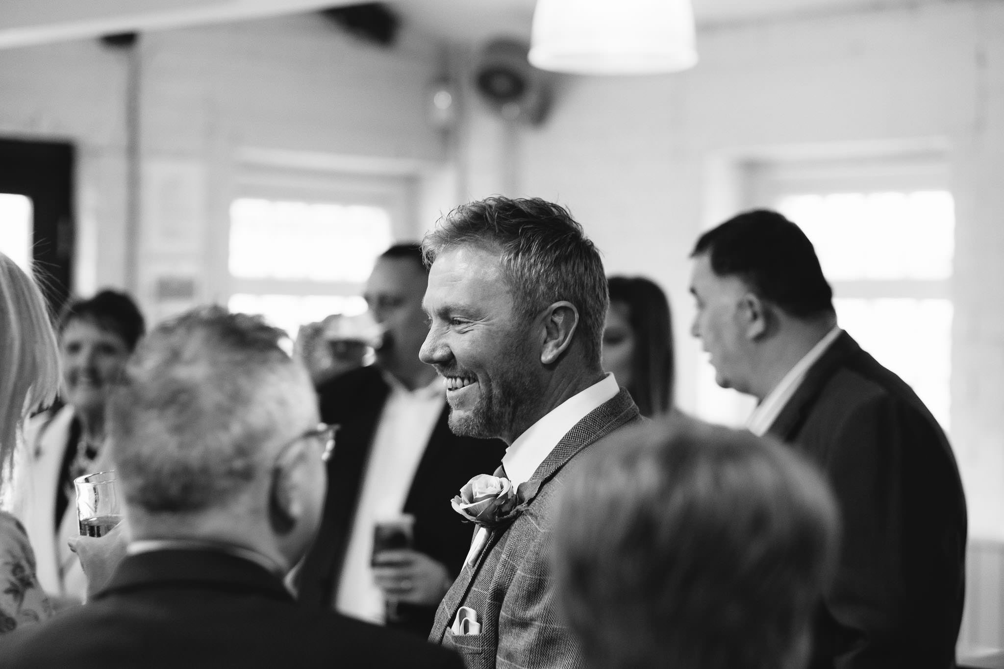 Black and white photo of groom laughing before wedding ceremony