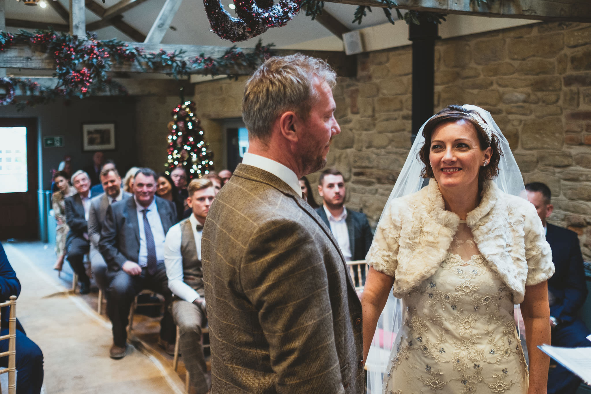 Bride smiling at groom during wedding ceremony in barn with wooden beams