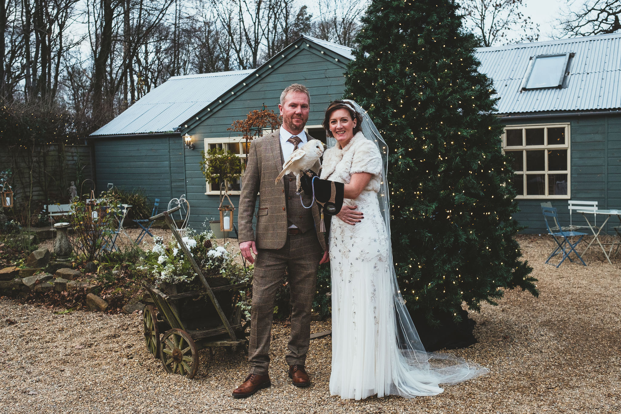 Bride and groom pose with owl in The Parlour at Blagdon courtyard