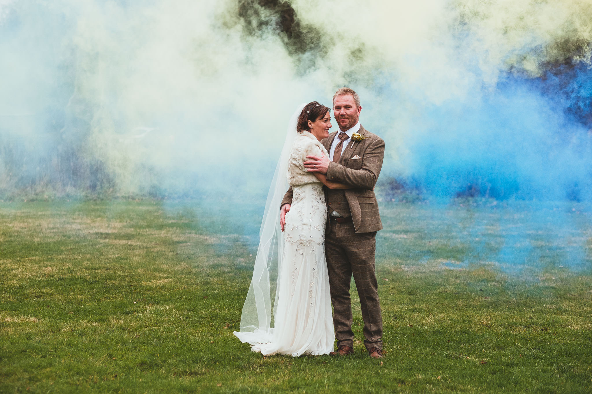 Bride and groom cuddling with coloured smoke billowing behind