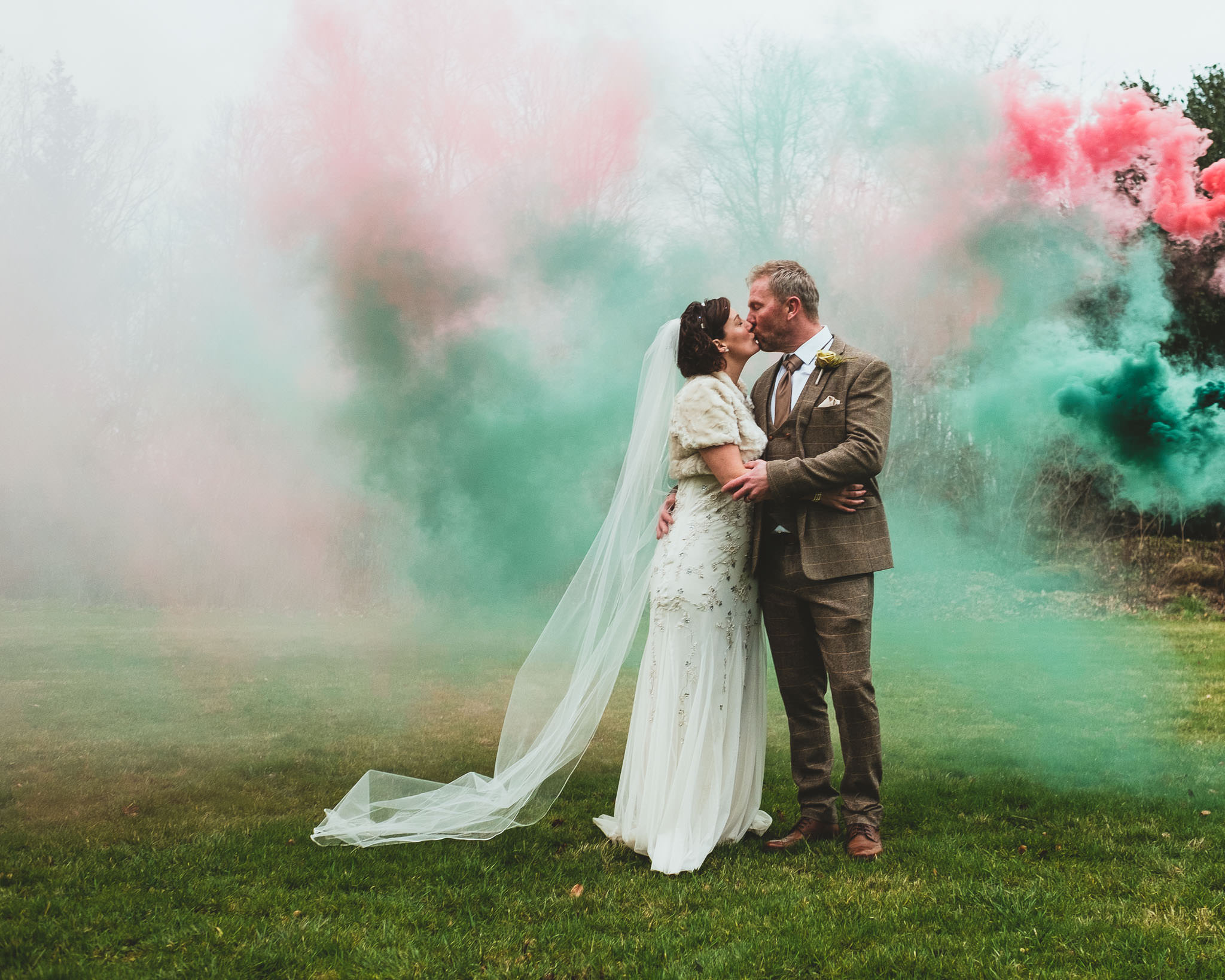 Bride and groom kiss while clouds of coloured smoke drift behind