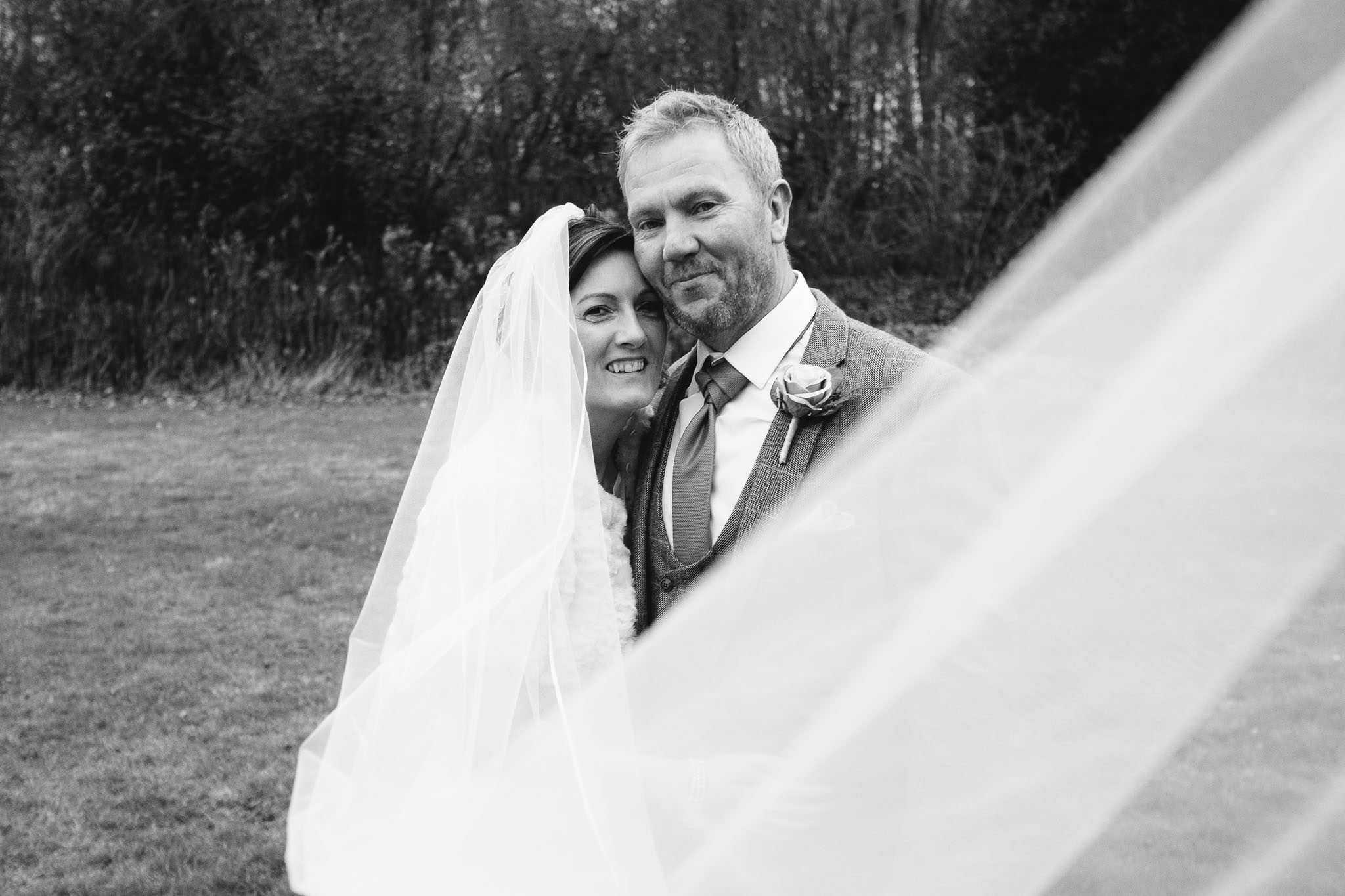 Black and white photo of the bride and groom with the veil blowing towards camera