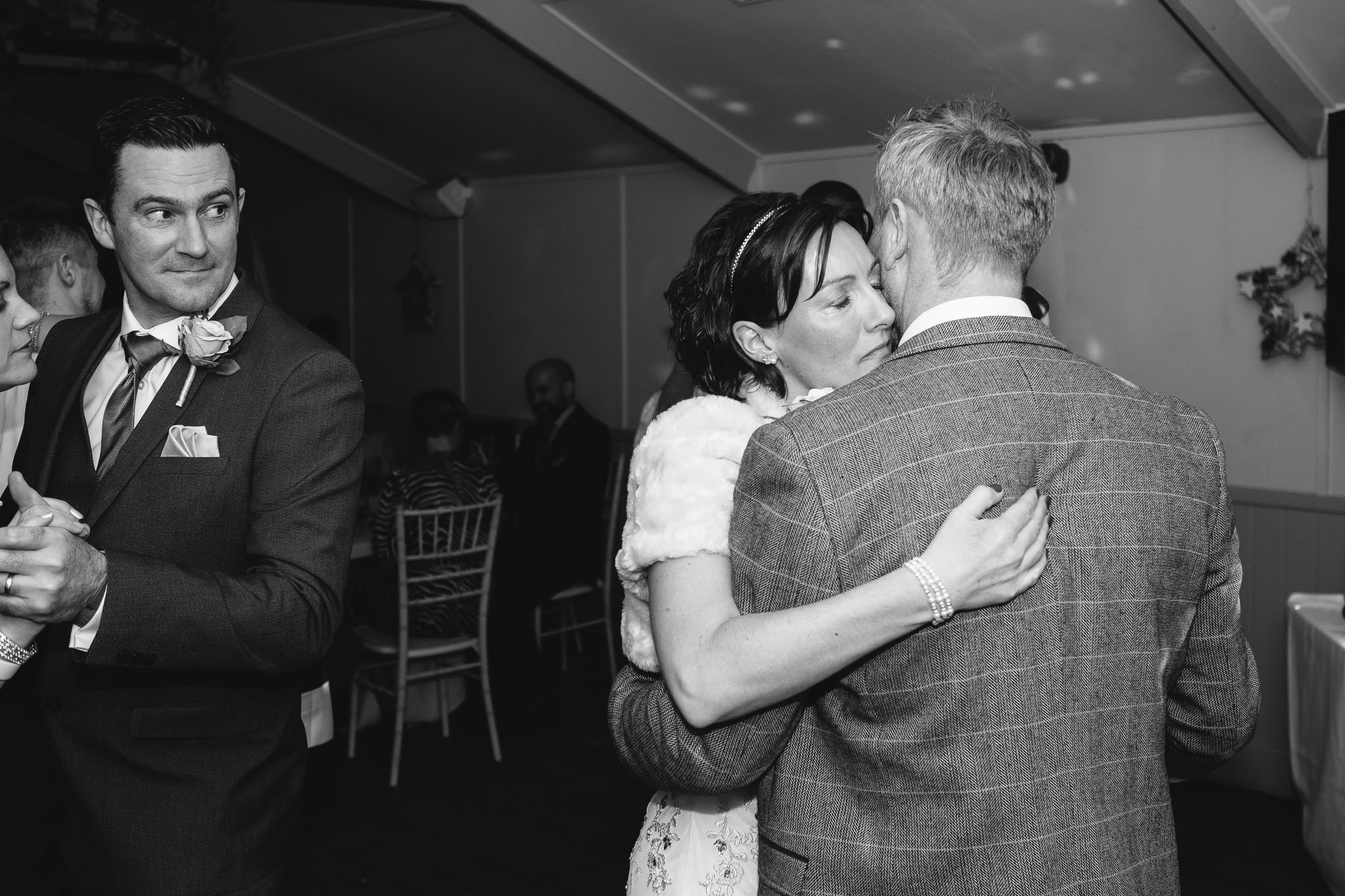 Black and white photo of the bride and groom dancing while guests look on