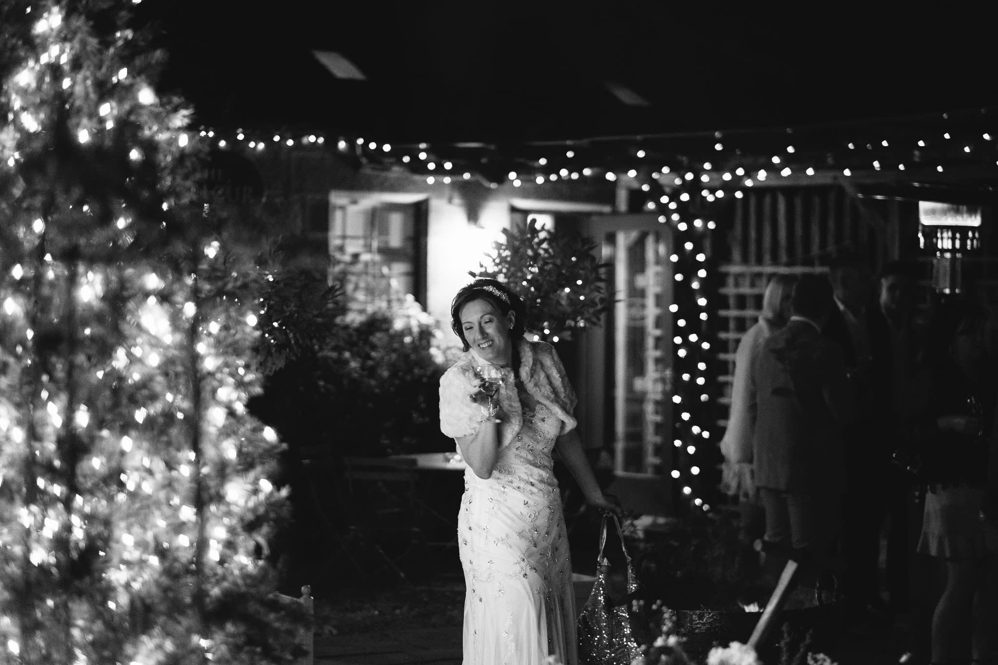 Black and white photo of bride pulling funny face with fairy lights behind