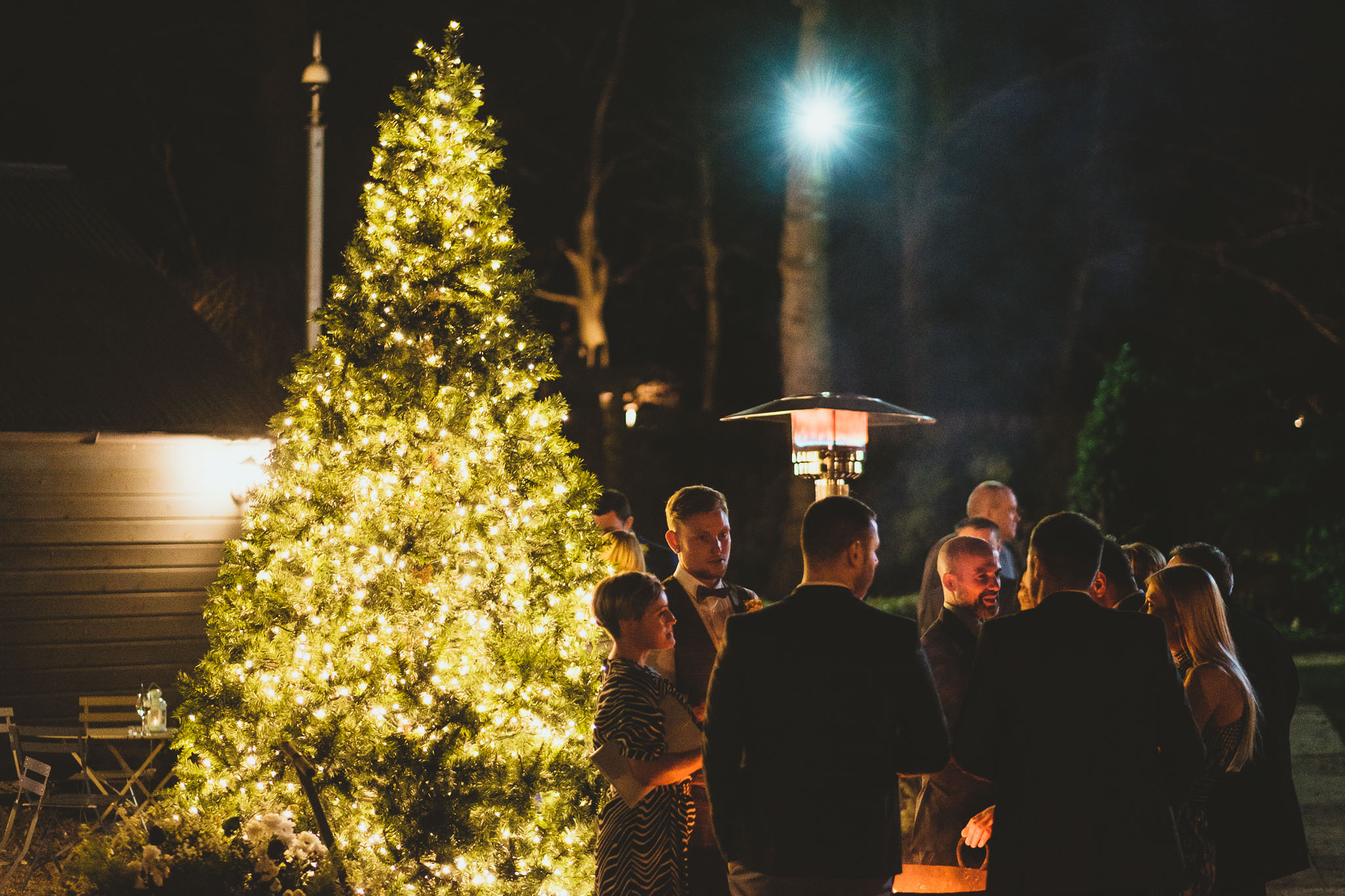 Wedding guests chat in the courtyard of The Parlour at Blagdon lit by Christmas tree