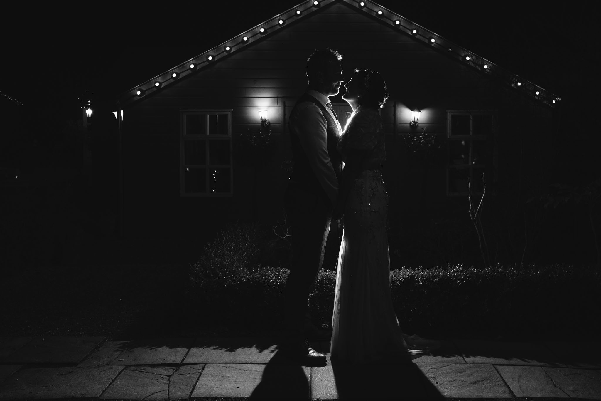 Black and white photo of bride and groom posing romantically in the courtyard of The Parlour at Blagdon