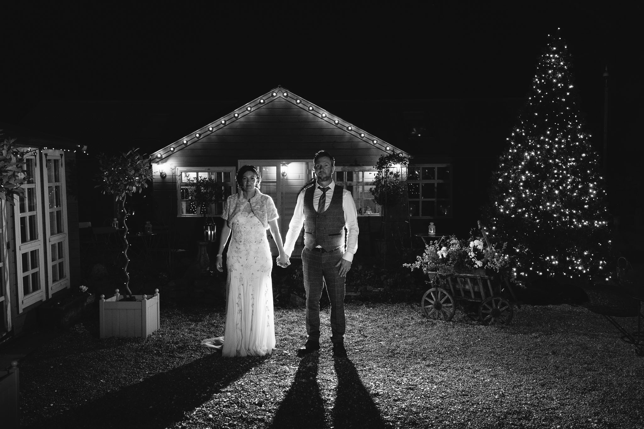 Black and white photo of the bride and groom holding hands at The Parlour at Blagdon