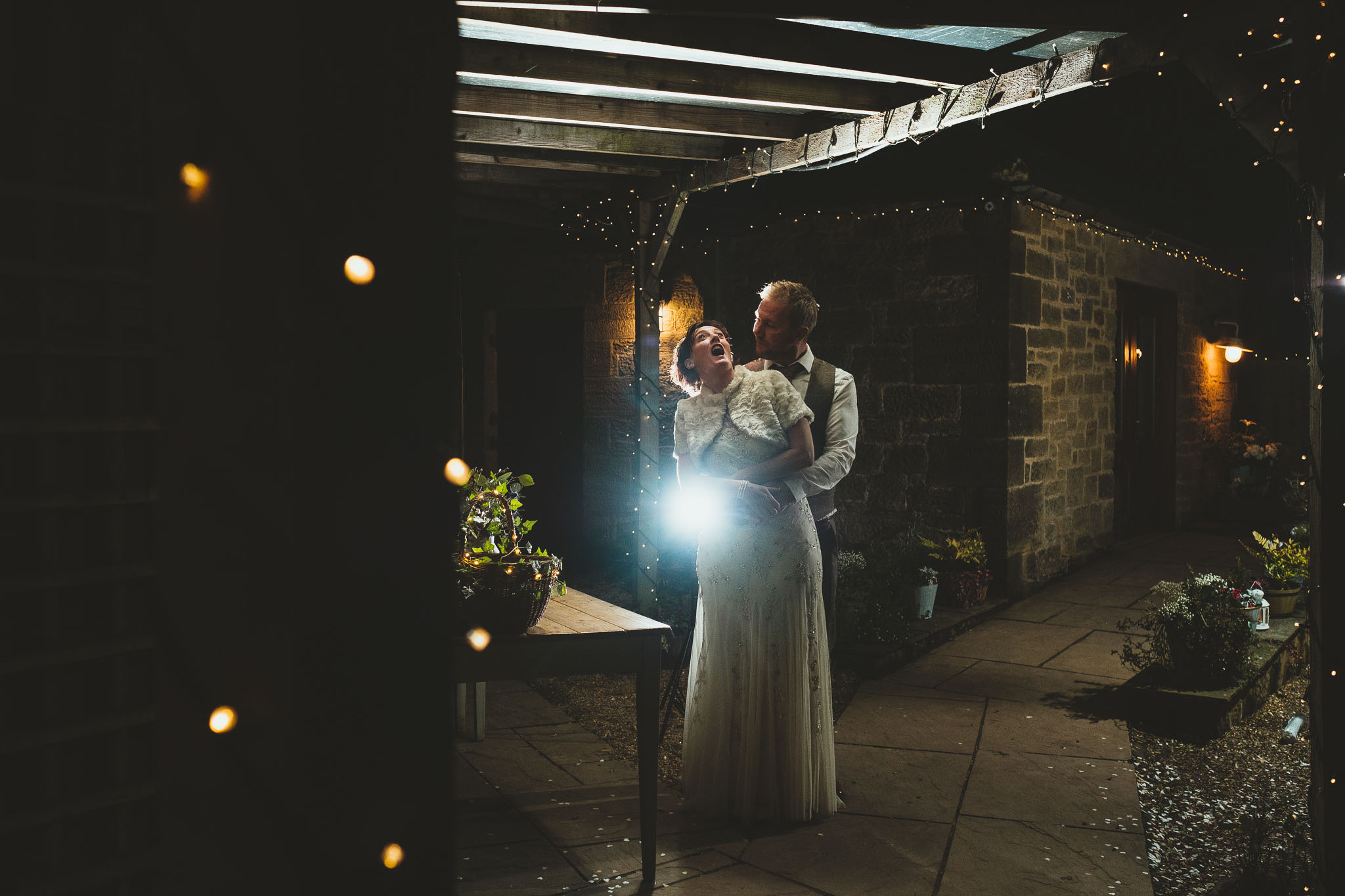 Funny nighttime portrait of bride and groom pulling faces