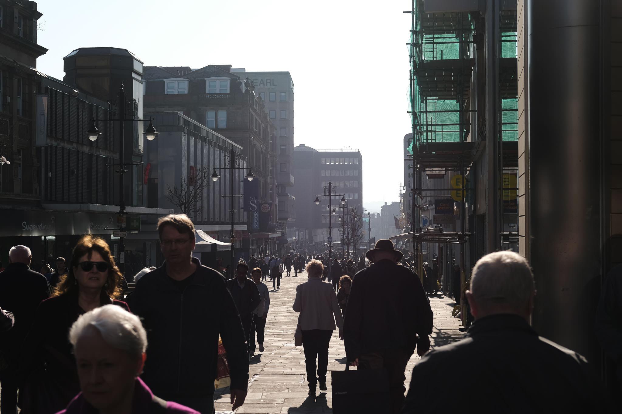 A man in a hat walks down Northumberland Street in Newcastle in low winter sun