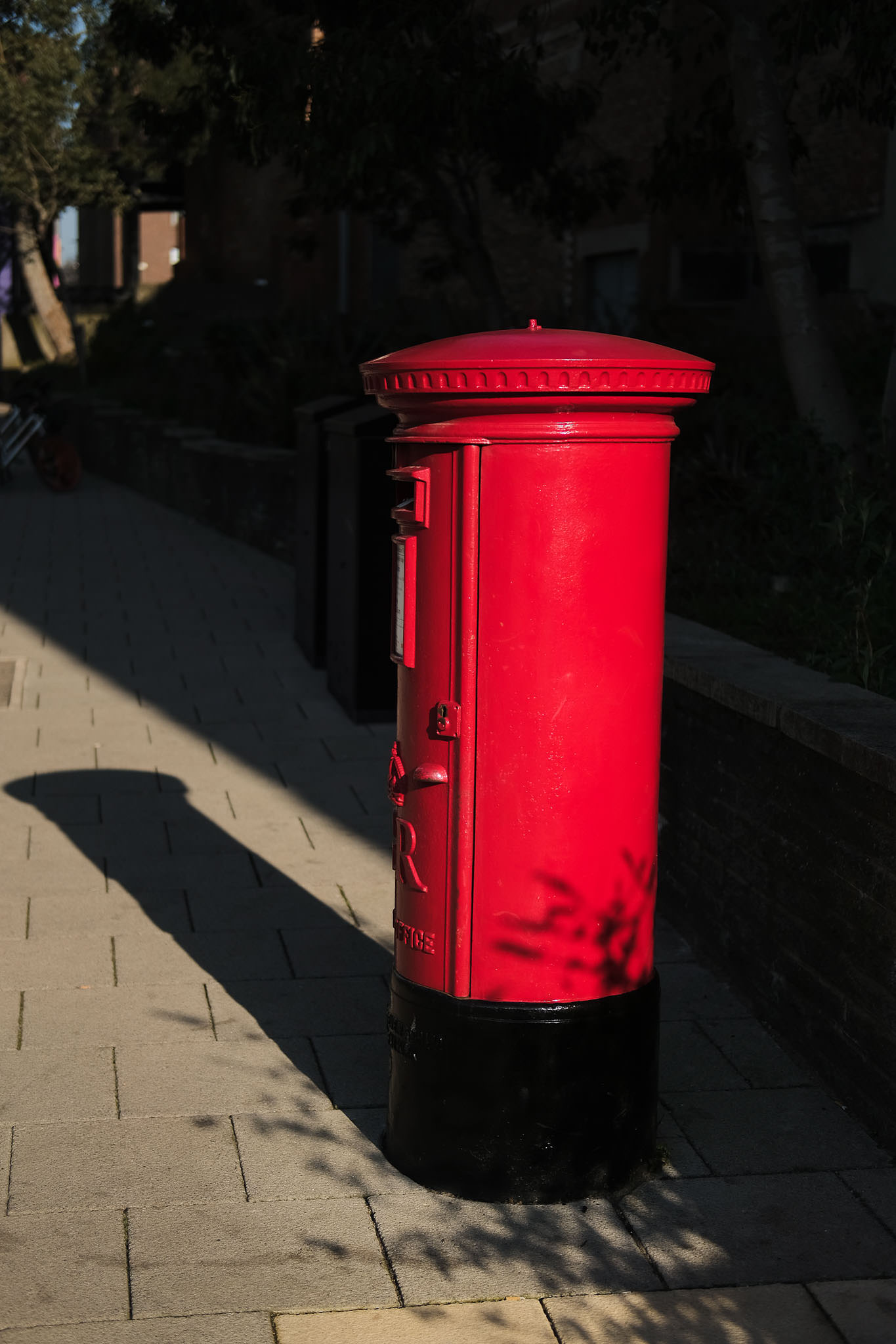 Vibrant red post box casts deep dark shadow