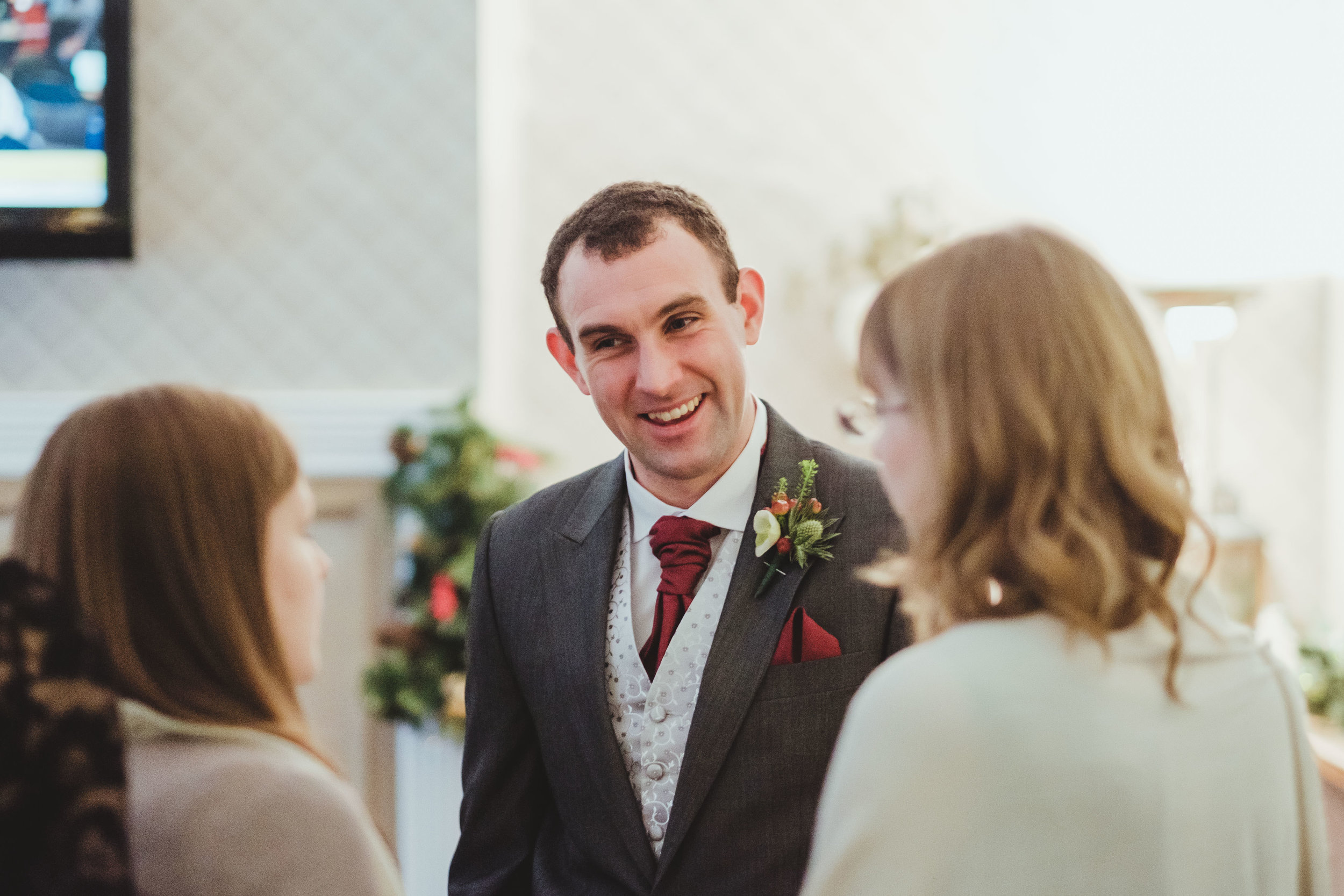 Groom laughs with wedding guests