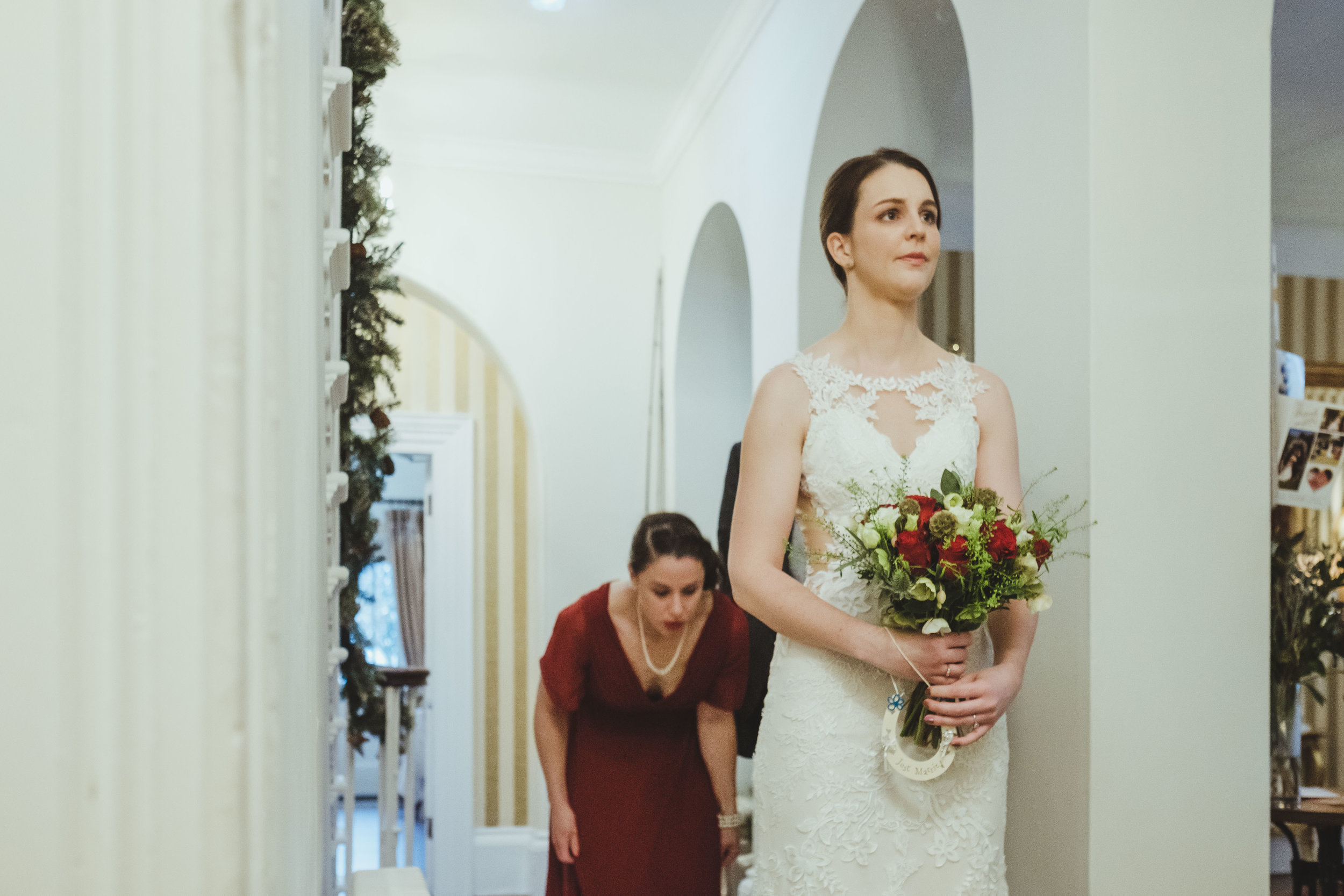 Bride's dress being prepped by bridesmaid before wedding ceremony