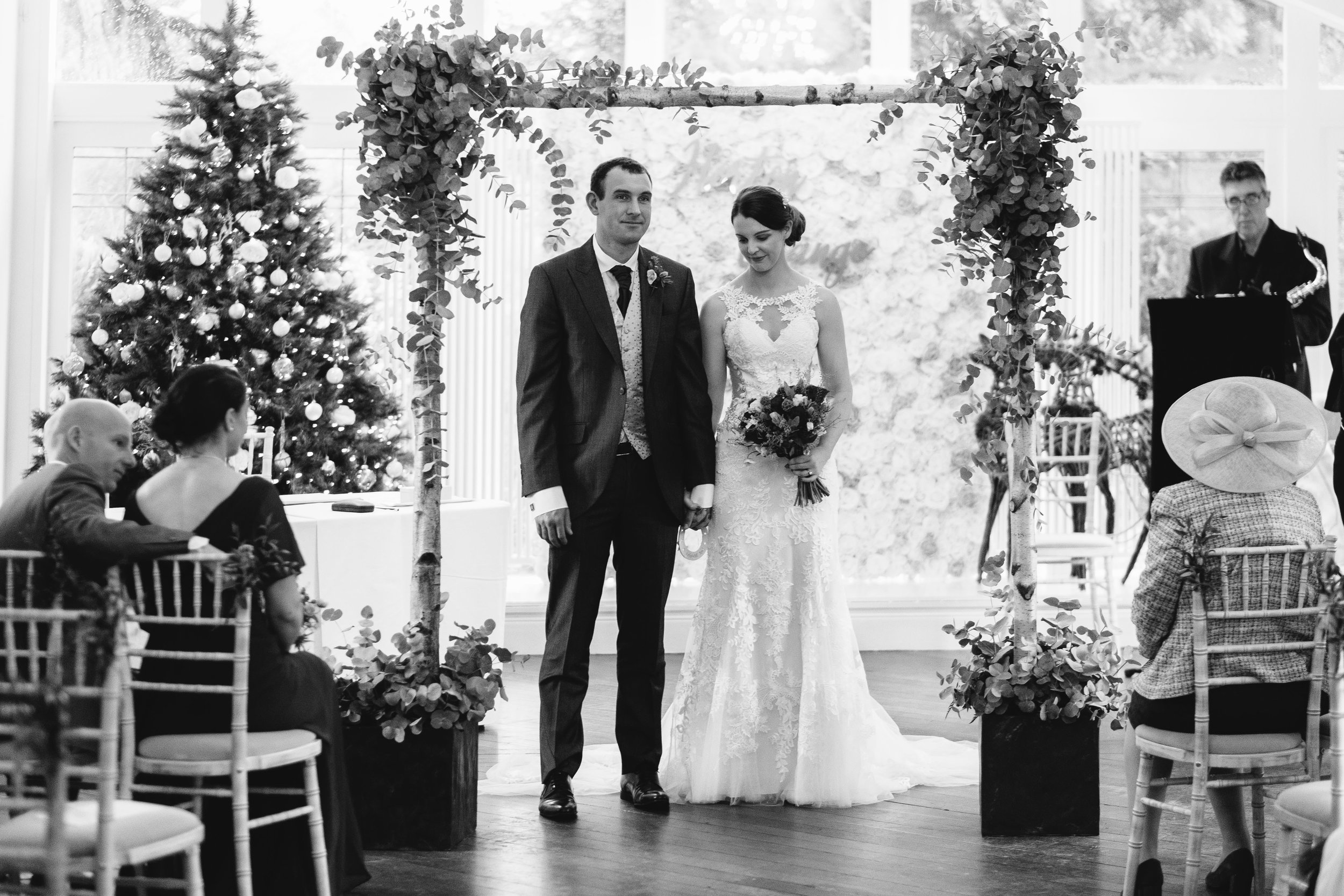 A black and white photo of the bride and groom standing under a flower arch at Horton Grange