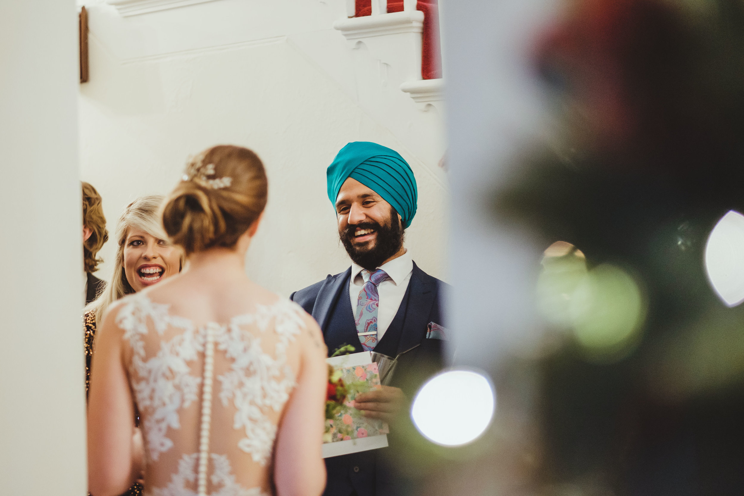 Bride chats with wedding guest wearing turban with Christmas tree lights in foreground