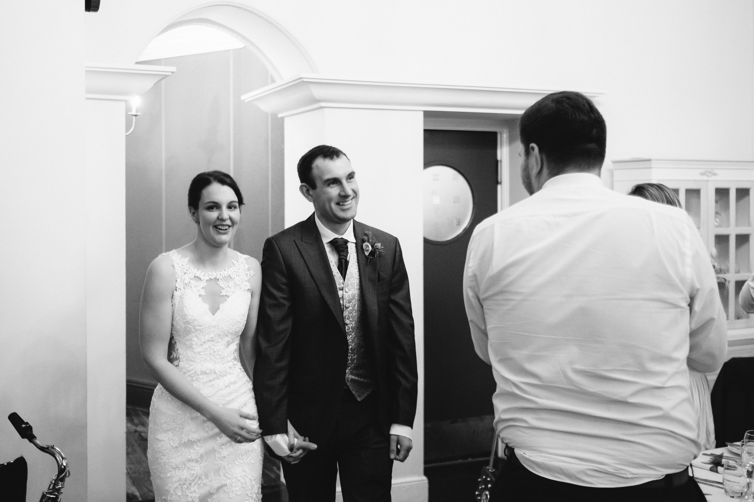 A black and white photo of the bride and groom entrance for the wedding breakfast
