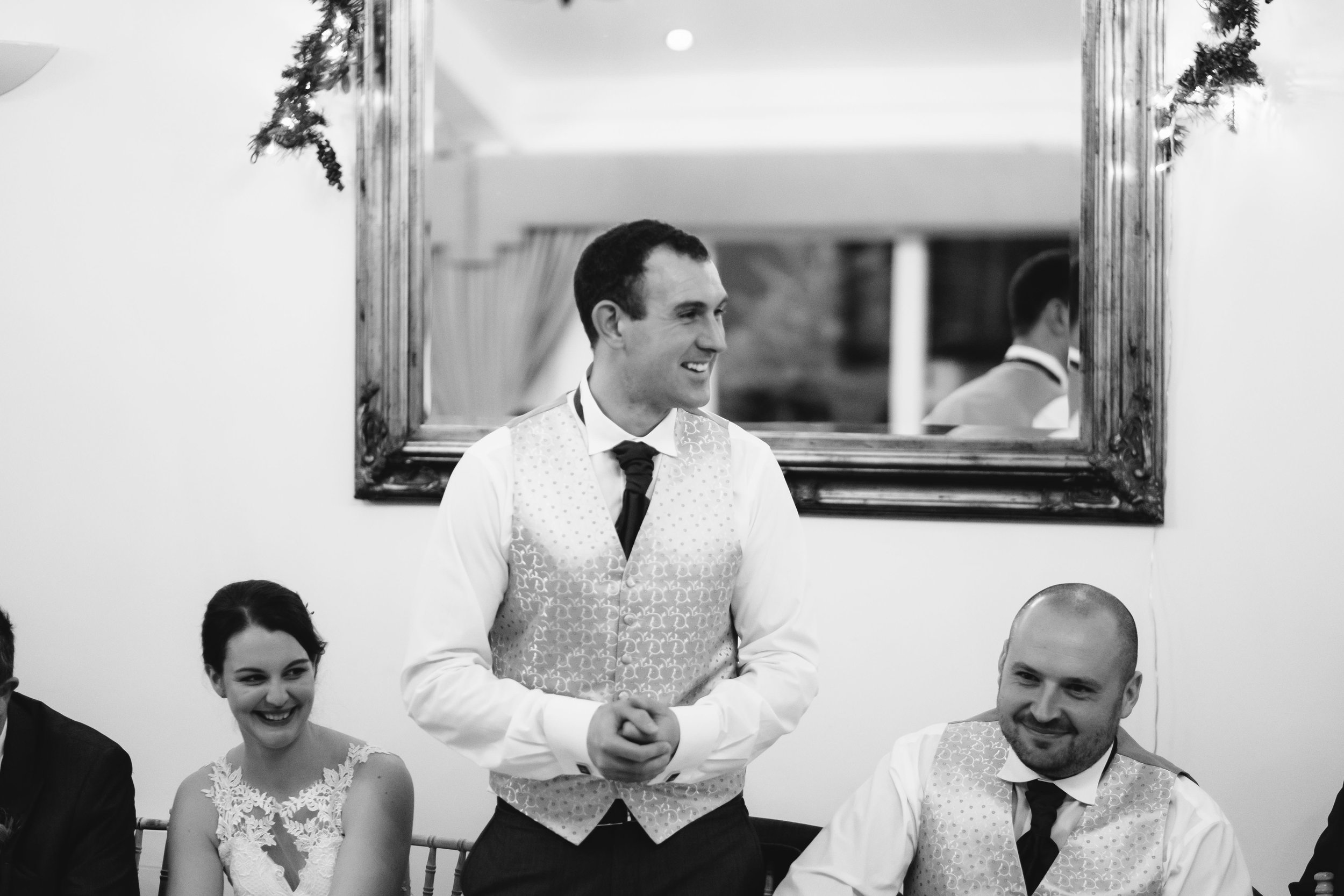 A black and white photo of the groom giving a wedding speech