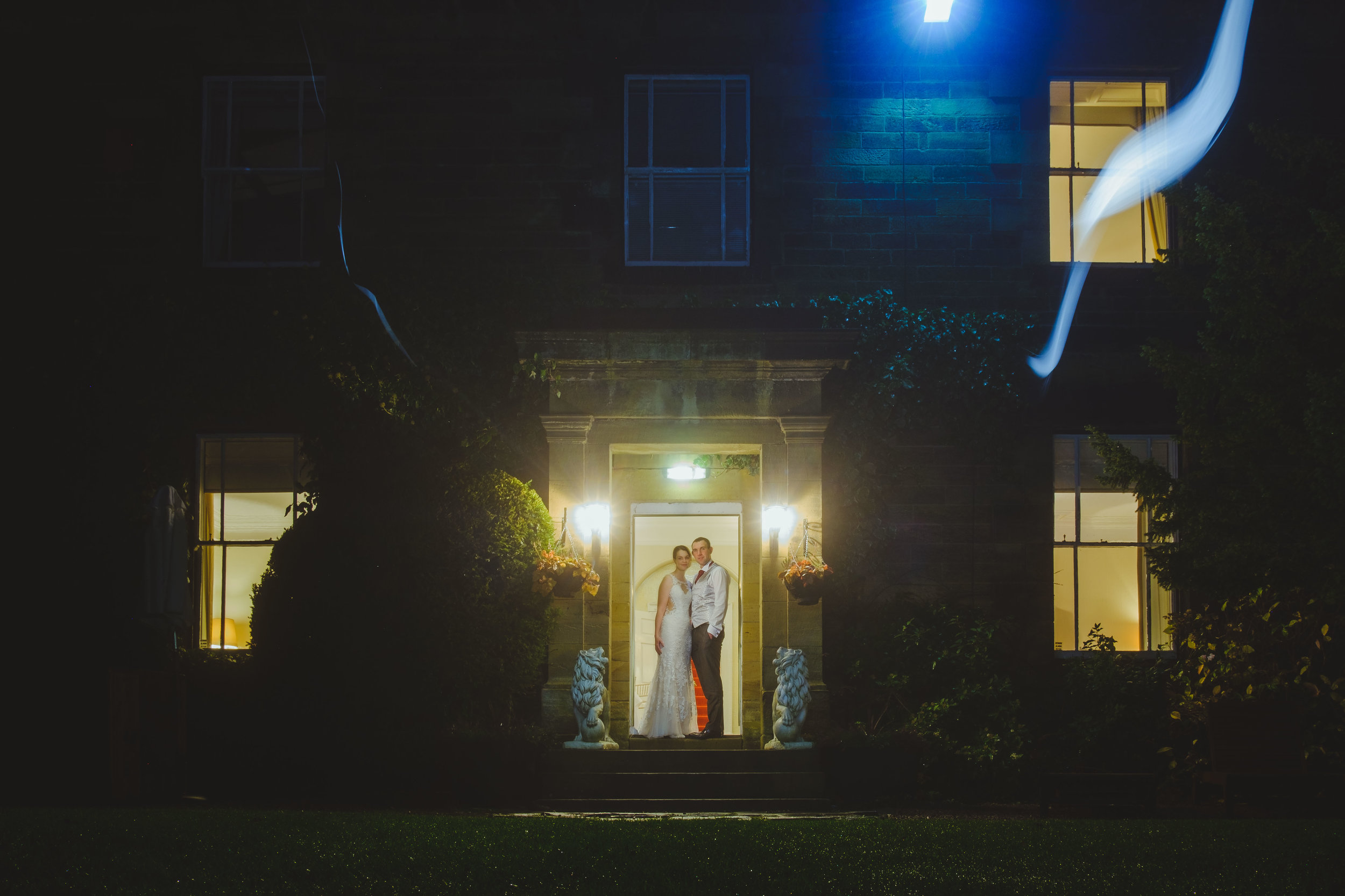 Couple pose at night in doorway of Horton Grange in Northumberland