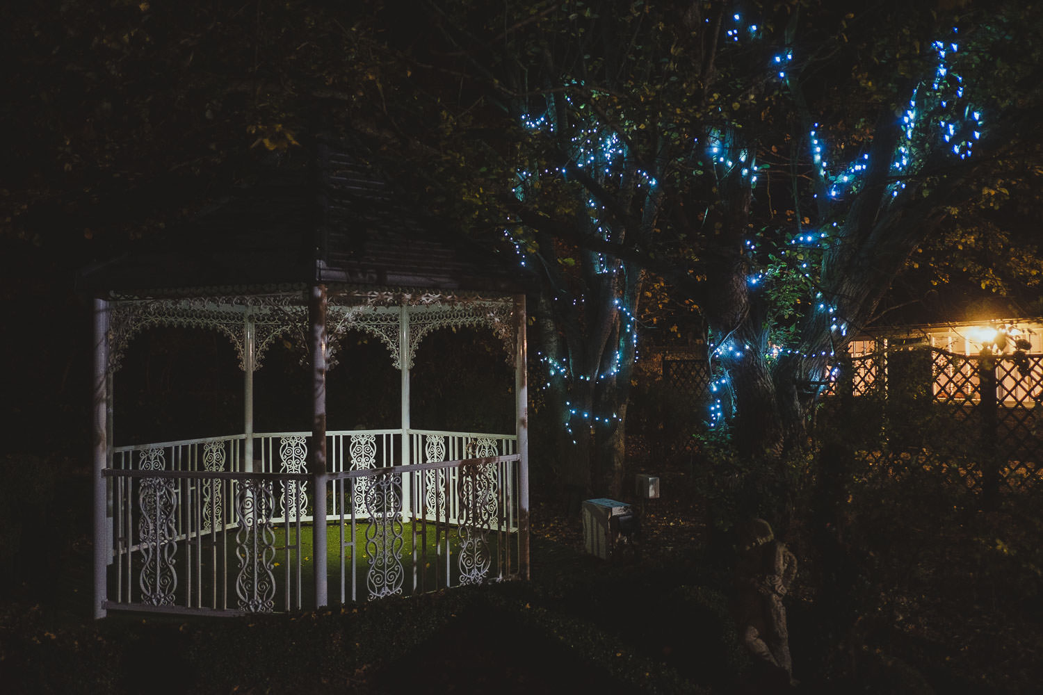 The gazebo lit up at night by fairy lights in the trees.
