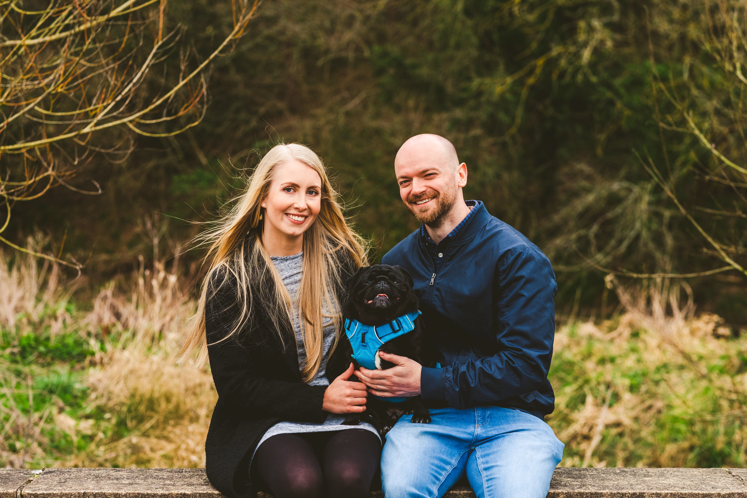 Engaged couple sit on wall in Newcastle holding black pug
