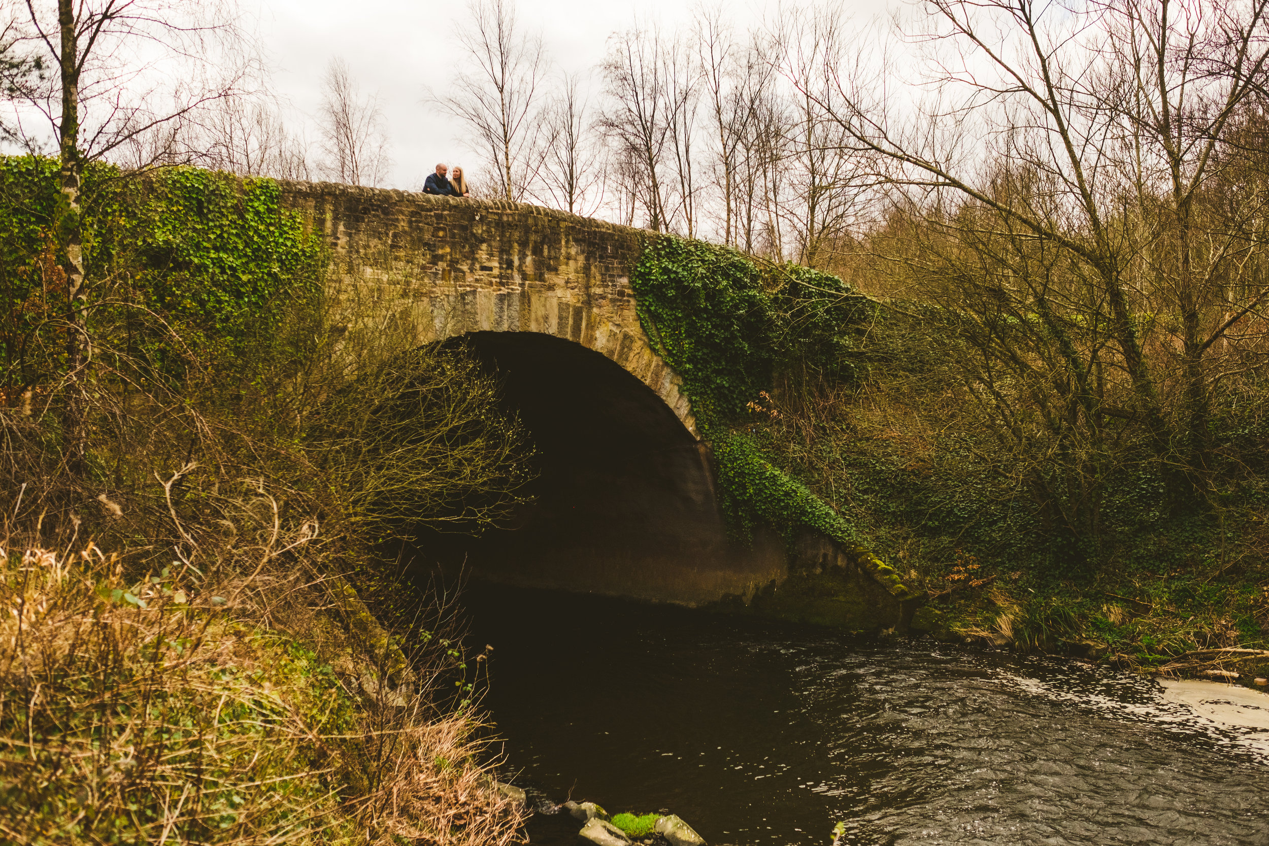 Couple stand on hump back bridge with stream running underneath in Newcastle