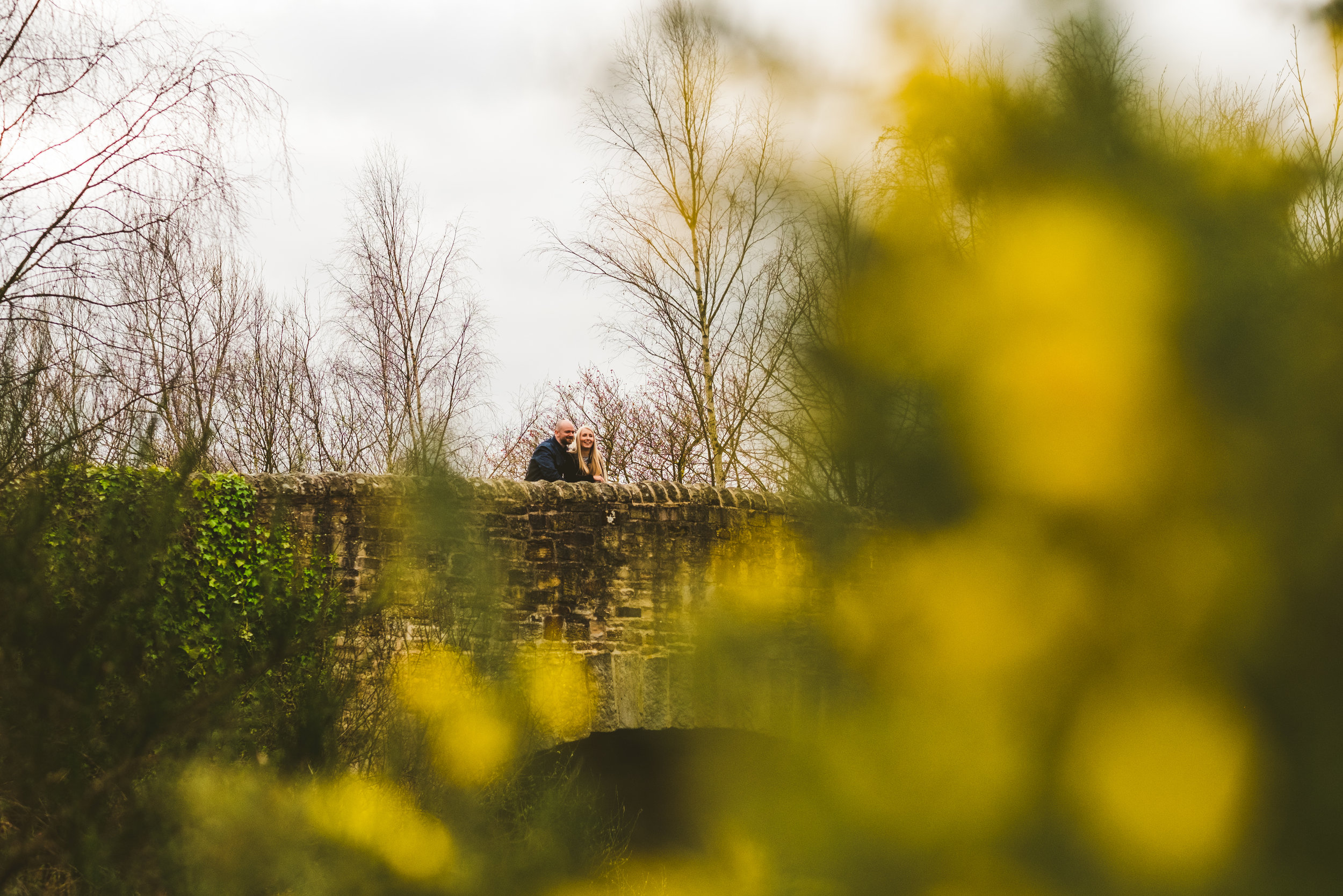 Couple pose on bridge in Derwent Park with yellow gorse in foreground