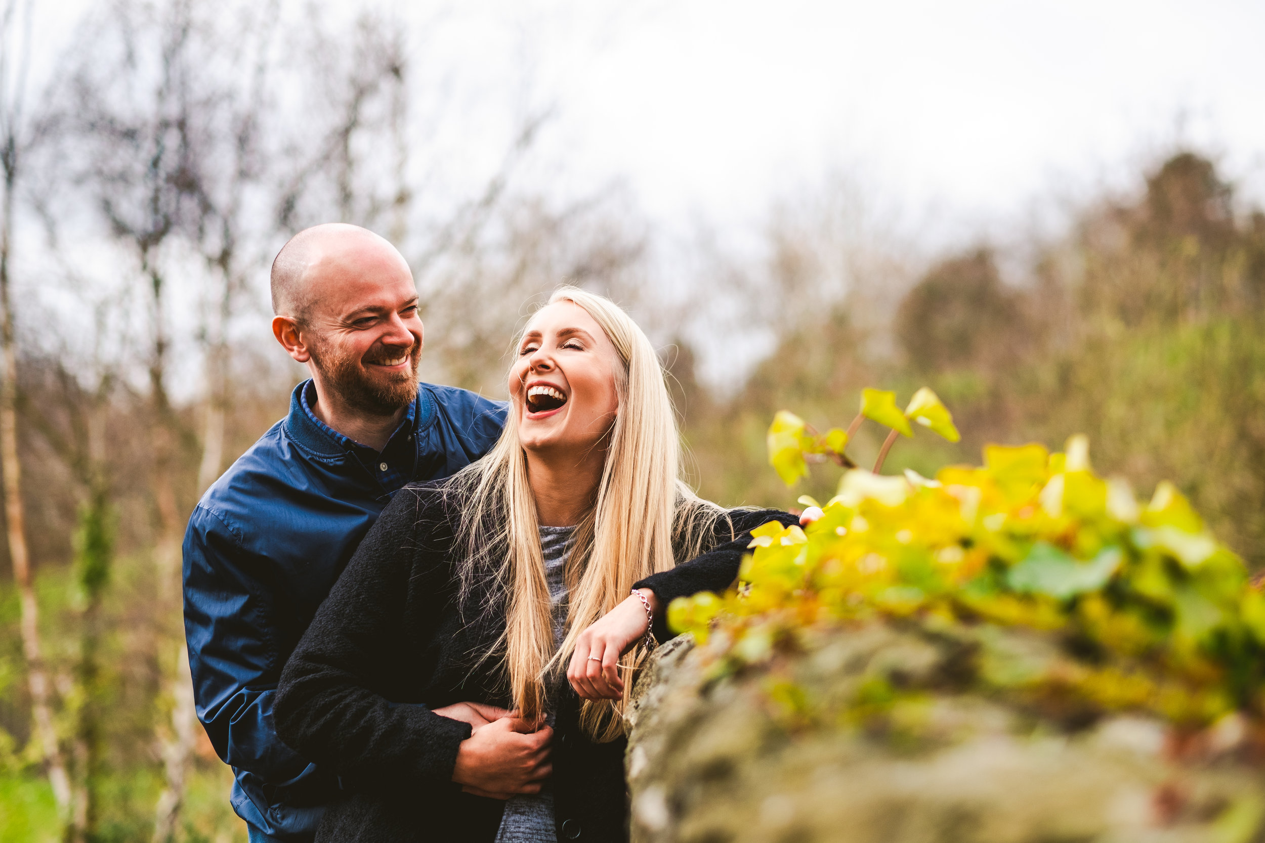 Couple roar with laughter while leaning against wall in Newcastle