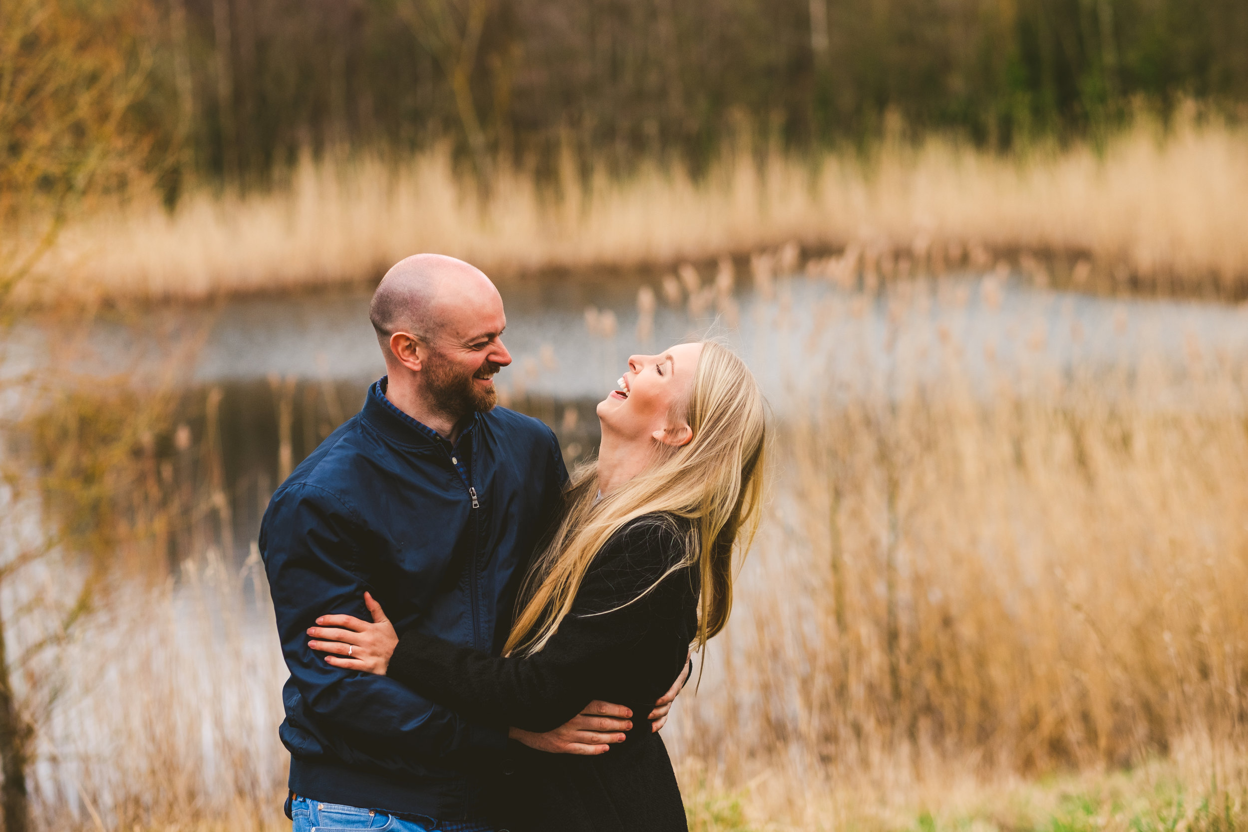 Engaged couple cuddle and laugh with pond in background on the Derwent walk